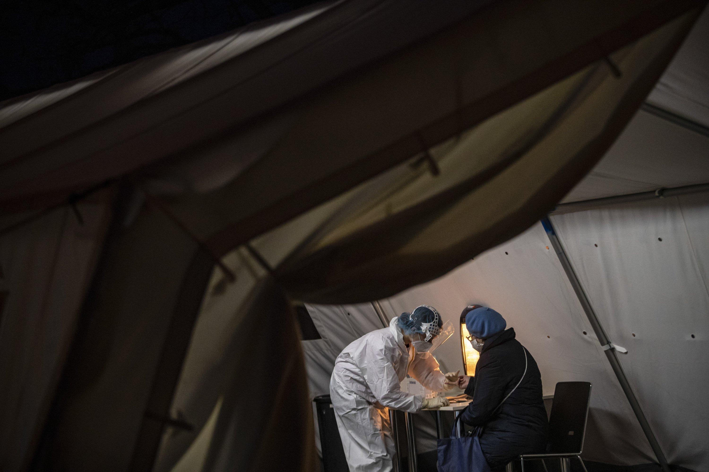 A medical worker wearing personal protective equipment (PPE) takes a sample from a woman for testing for coronavirus antibodies at drive-in coronavirus testing station in Prague, Czech Republic, Feb. 1, 2021. (EPA Photo)