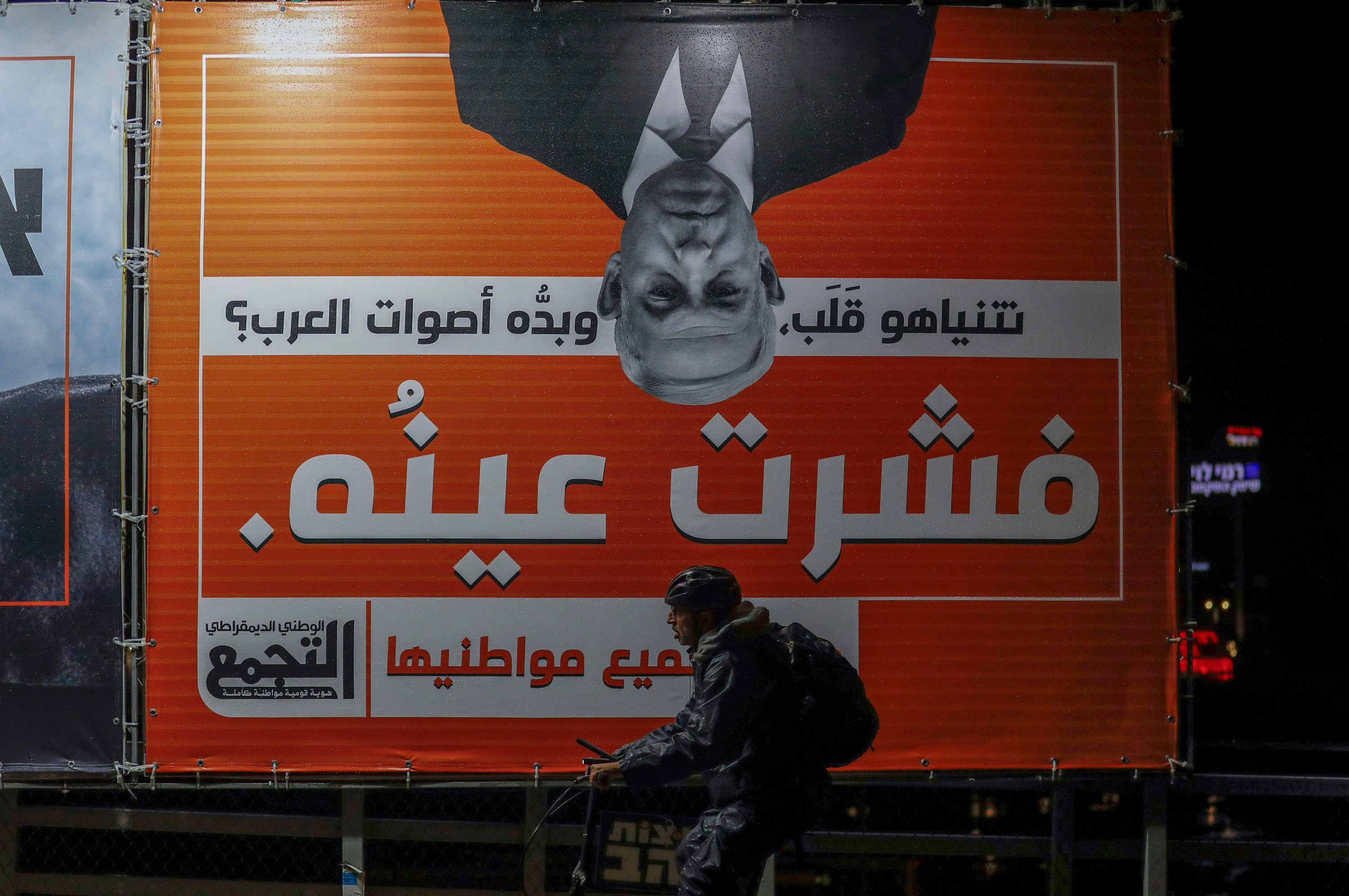 A man rides a bike past a campaign billboard for the Balad Party, part of the Arab Joint List that reads in Arabic