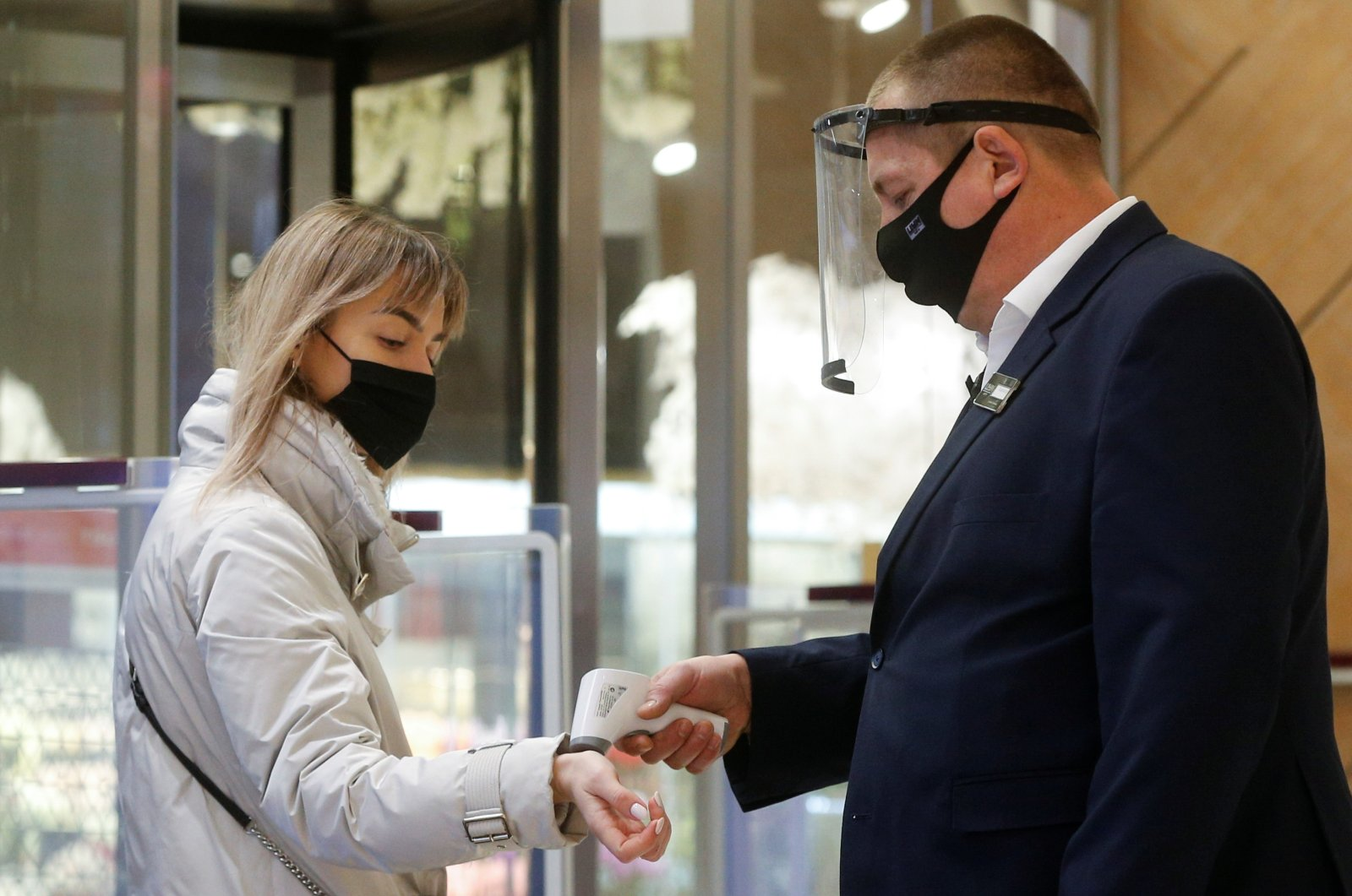 An employee wearing a mask and face shield checks the body temperature of a visitor at the Central Universal Department Store (TsUM), on the first day after ending a coronavirus lockdown, in Kyiv, Ukraine, Jan. 25, 2021. (Reuters Photo)