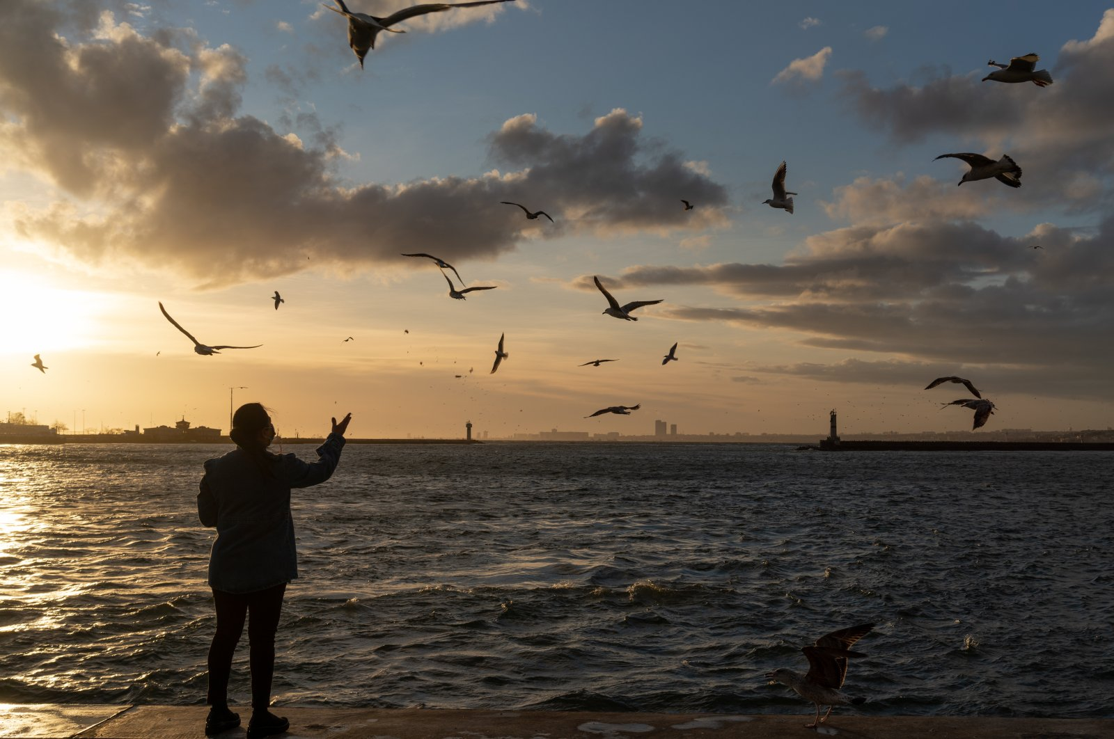 A woman standing by the sea feeds the birds, Istanbul, Turkey, Jan. 25, 2021. (Photo by Getty Images)