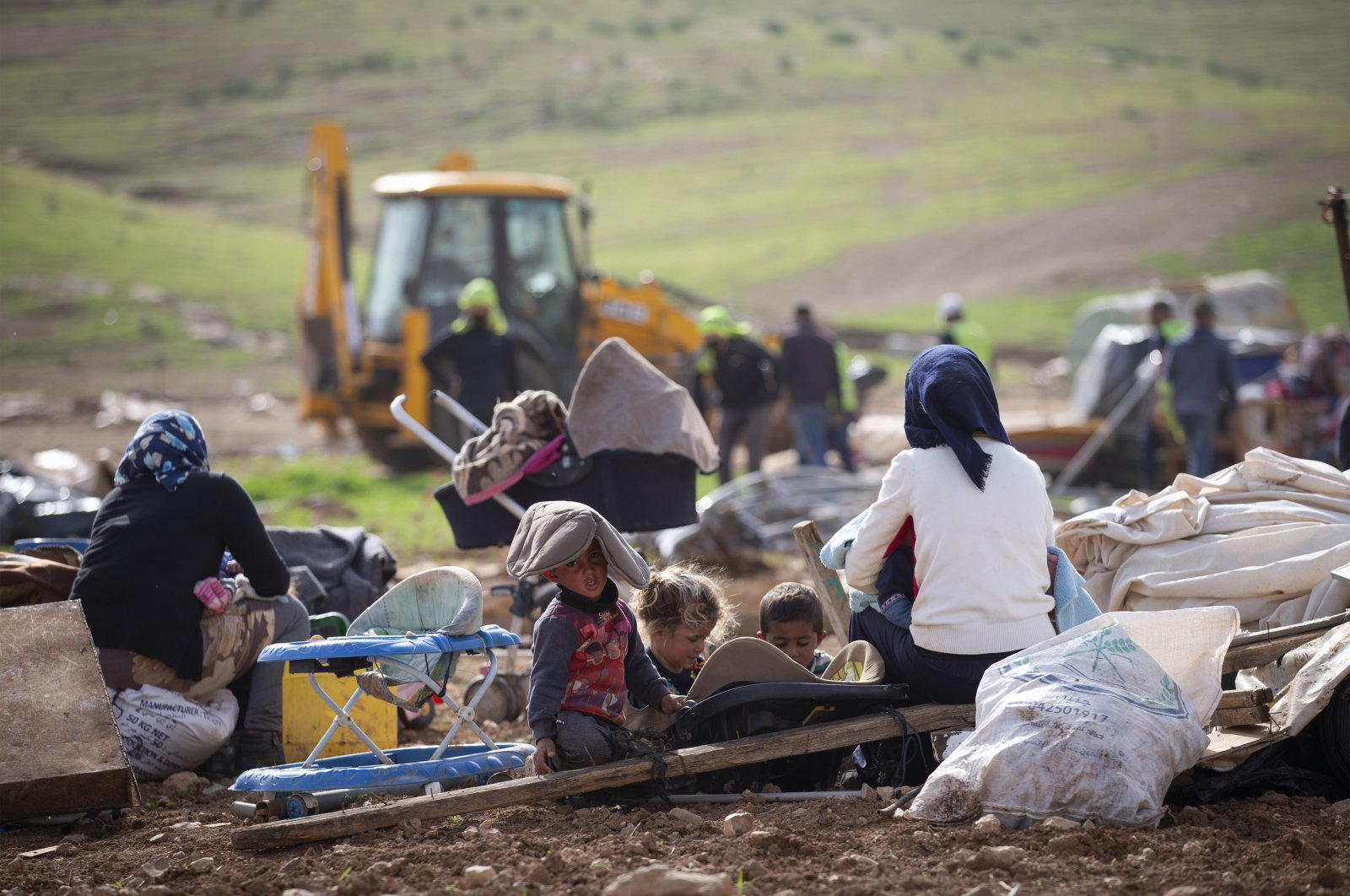 Palestinians watch Israeli troops demolish tents and other structures at the Khirbet Humsu hamlet in the Jordan Valley in the occupied West Bank, Palestine, Feb. 3, 2020. (AP Photo)