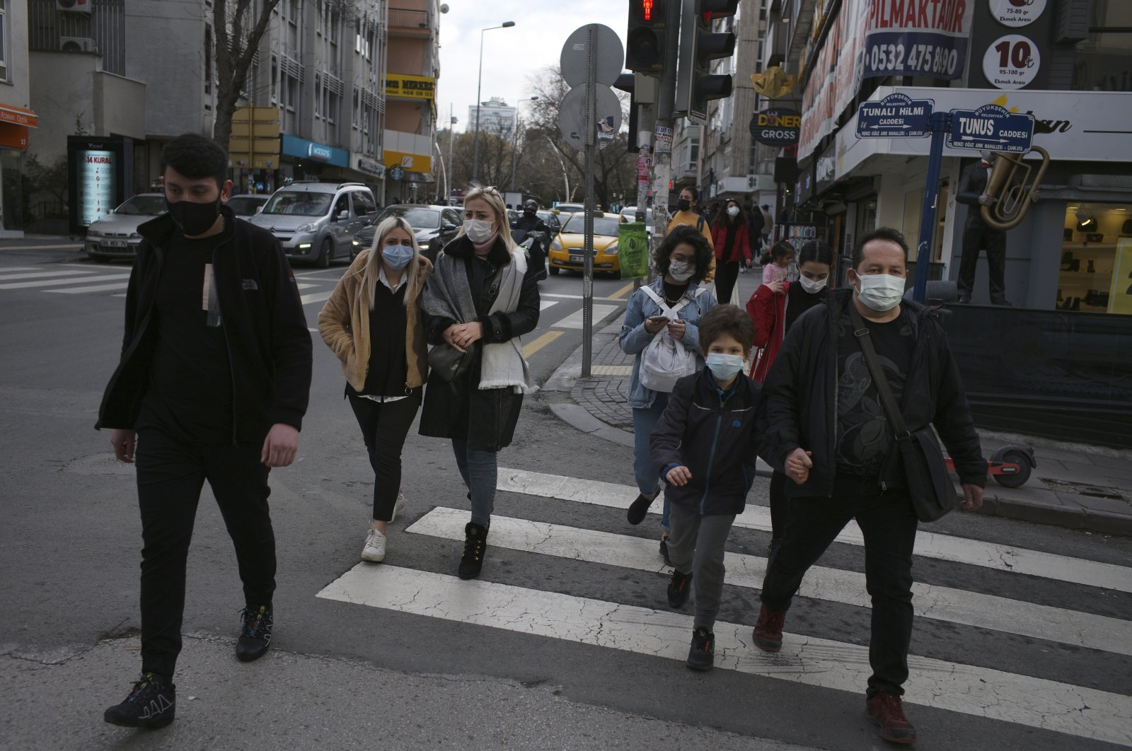 People wearing protective masks walk on a street in the capital Ankara, Turkey, Feb. 2, 2021. (AP Photo)