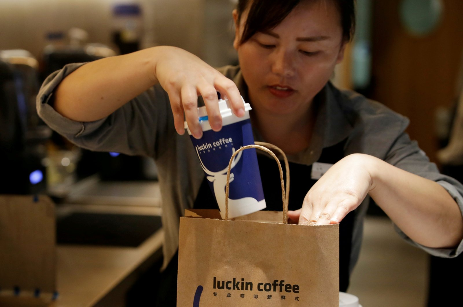 A barista packs a coffee at a Luckin Coffee shop in Beijing, China, July 17, 2018. (Reuters Photo)
