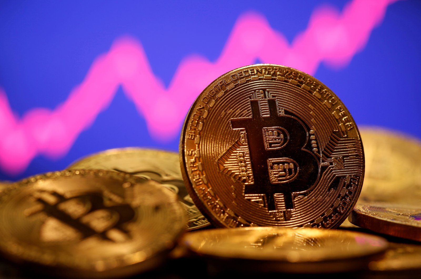 A representation of virtual currency Bitcoin is seen in front of a stock graph in this illustration taken Jan. 8, 2021. (Reuters Photo)