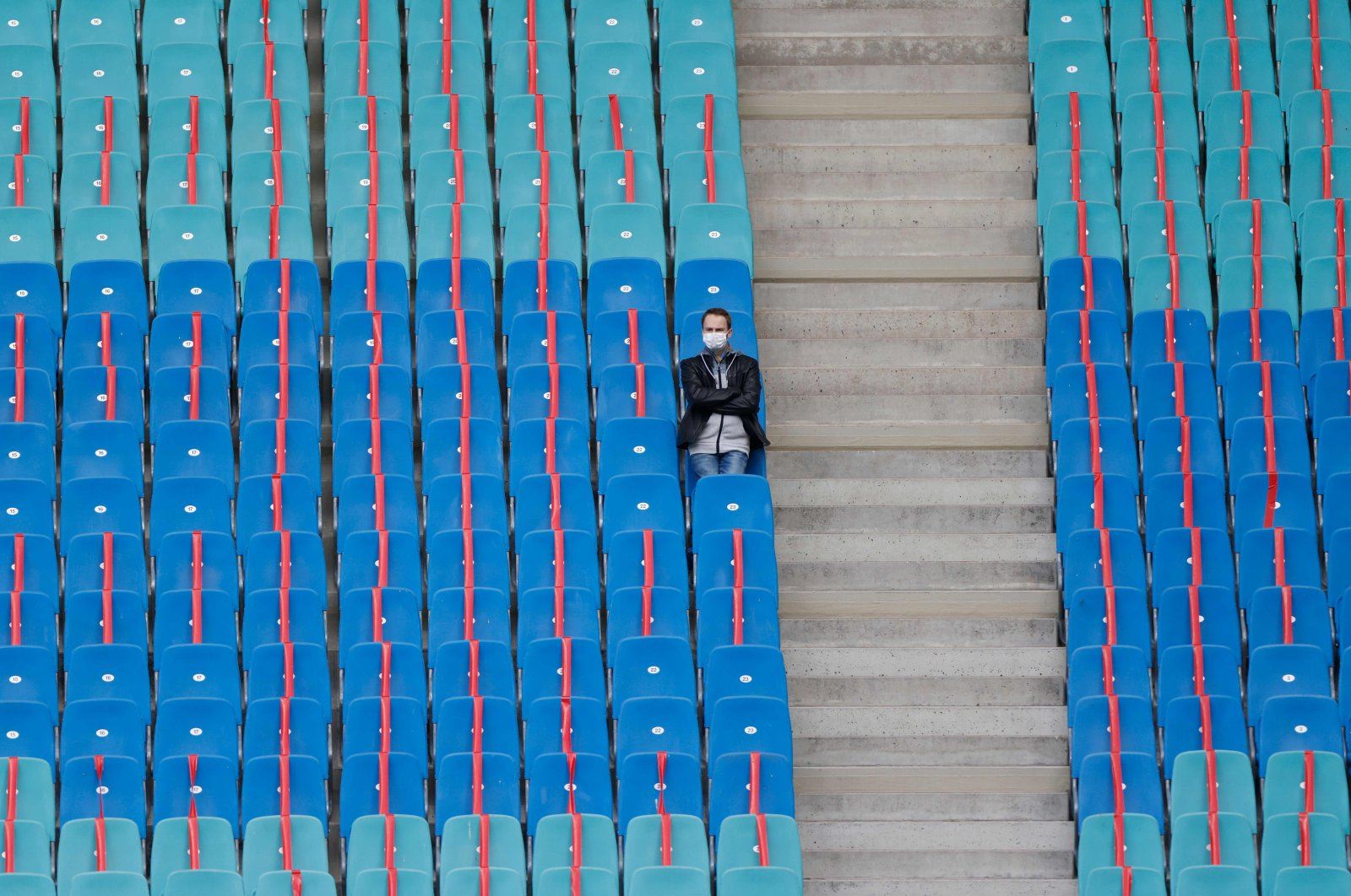 Red ribbons are placed on the spectator's seats to maintain social distancing as a man is seen alone in a tribune at the stadium in Leipzig, eastern Germany, Oct. 24, 2020.