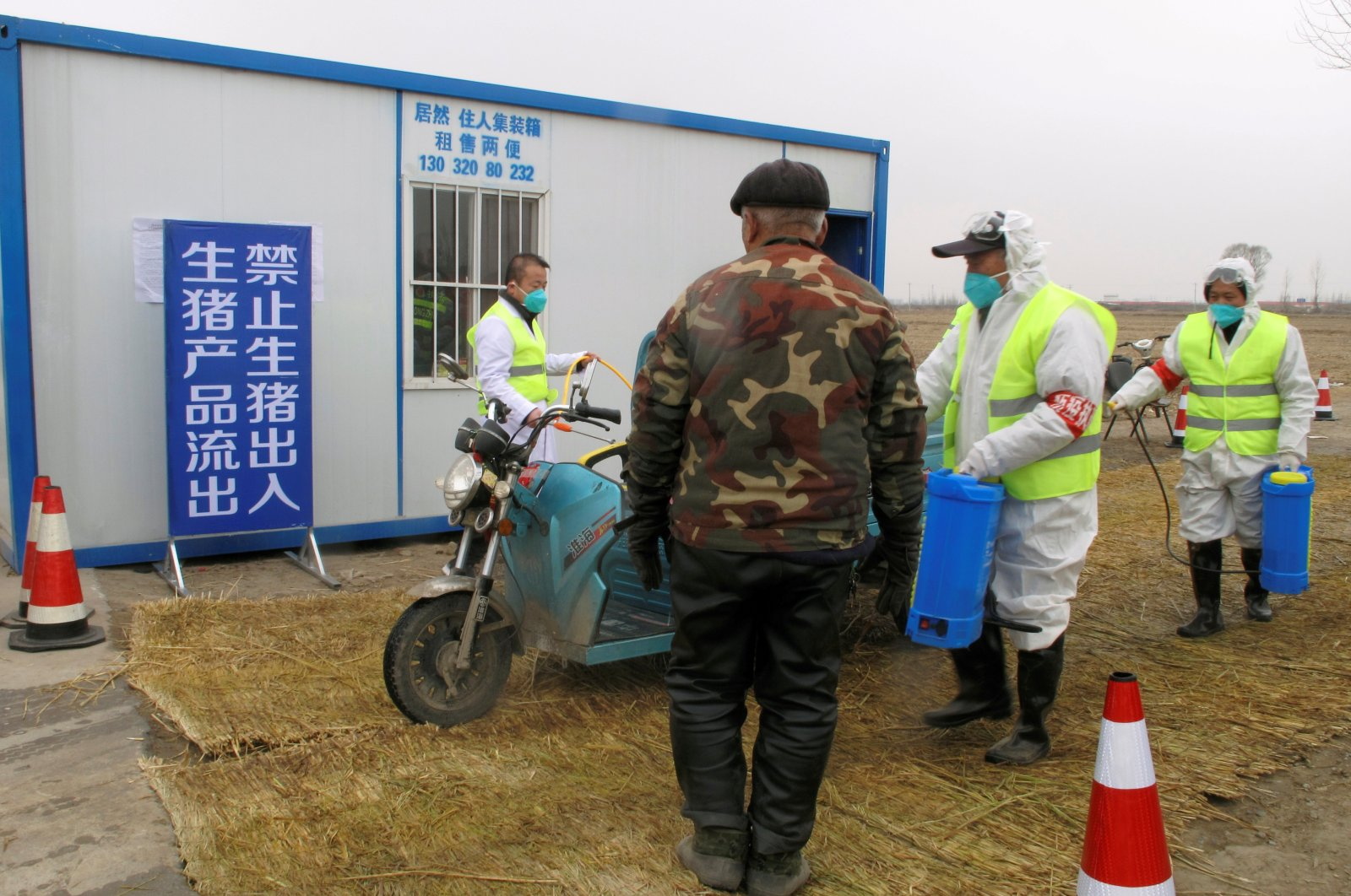 Workers in protective suits disinfect a vehicle at a checkpoint, leading to a farm owned by Hebei Dawu Group where African swine fever was detected, in the Xushui district of Baoding, Hebei province, China, Feb. 26, 2019. (REUTERS Photo)