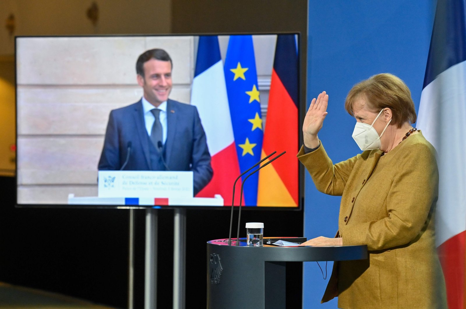 French President Emmanuel Macron (L) seemingly watches German Chancellor Angela Merkel wave at the end of a press conference after German-French Security Council video talks, Berlin, Germany, Feb. 5, 2021. (AFP Photo)