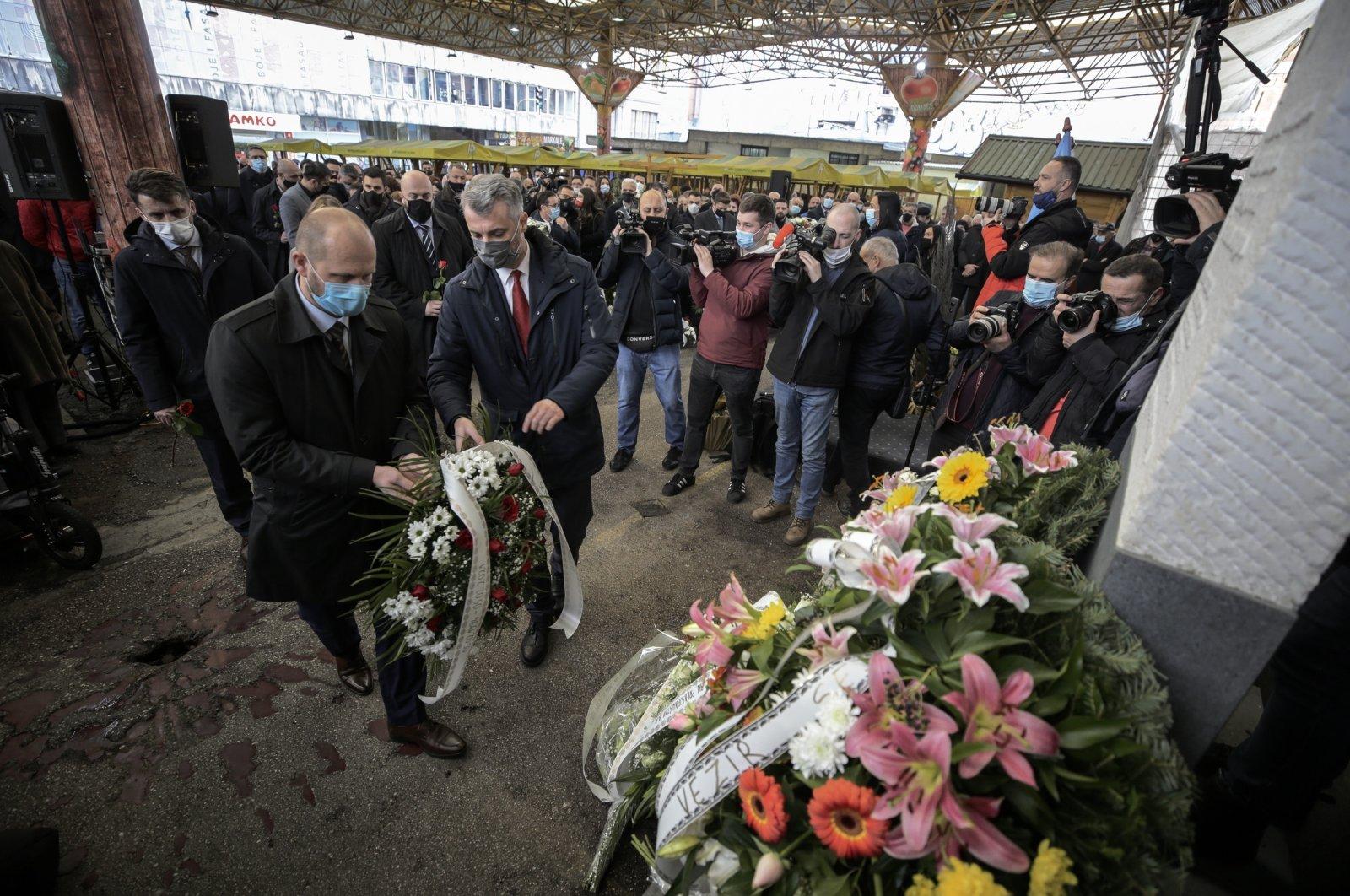 People leave flowers at the monument commemorating the Markale massacres in Sarajevo, Bosnia and Herzegovina, Feb. 5, 2021 (AA Photo)