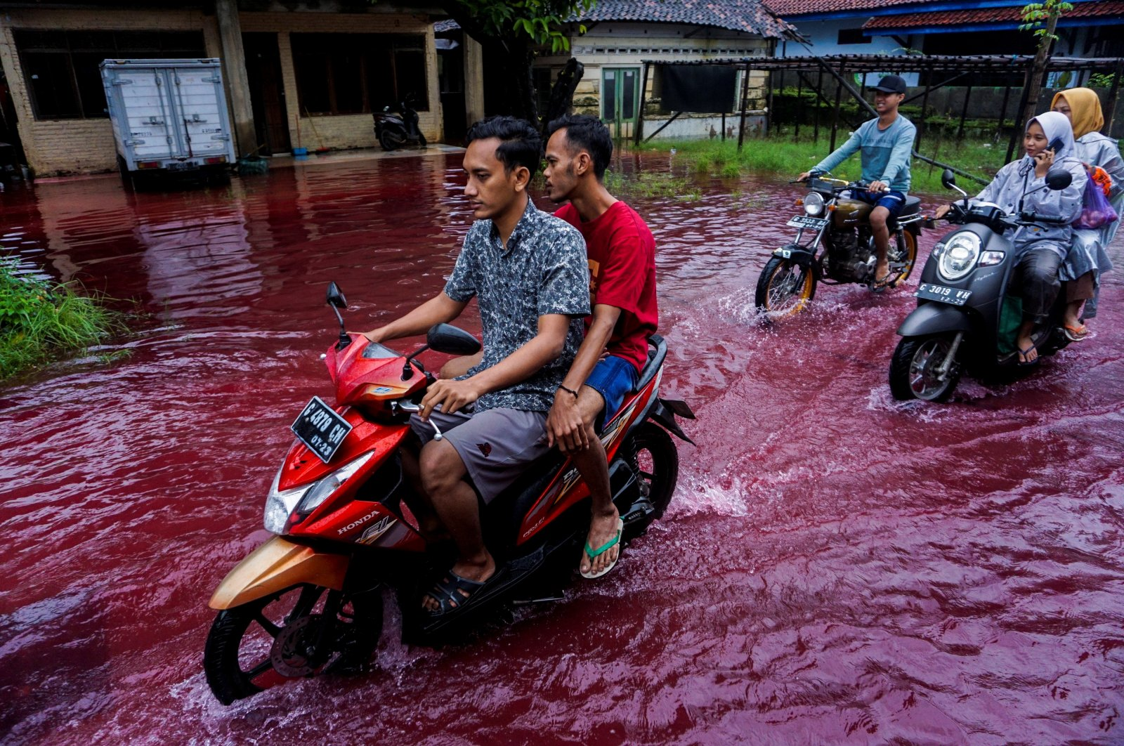 People ride motorbikes through a flooded road with red water due to the dye-waste from cloth factories, in Pekalongan, Central Java province, Indonesia, Feb. 6, 2021. (Reuters Photo)