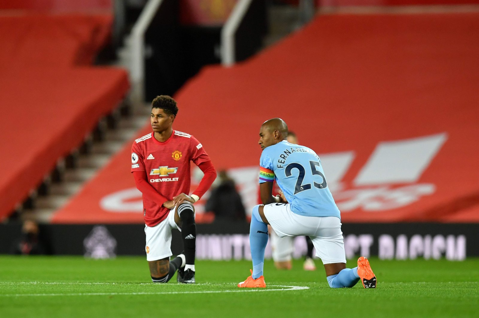 Manchester United's Marcus Rashford (L) and Manchester City's Fernandinho take a knee in support of the Black Lives Matter movement before the English Premier League football match between Manchester United and Manchester City, at the Old Trafford stadium in Manchester, England, Dec. 12, 2020. (AFP Photo)