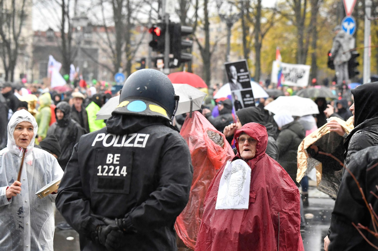 A police officer talks with protesters demonstrating against measures imposed by the German government to limit the spread of the coronavirus, close to the Reichstag building housing the Bundestag (the lower house of parliament) in Berlin, Germany, Nov. 18, 2020. (AFP Photo)