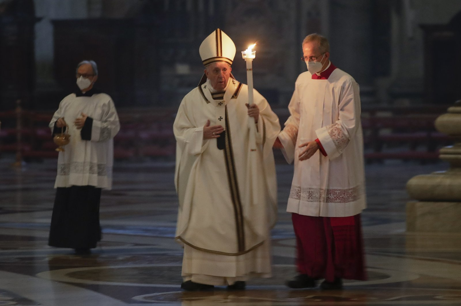 Pope Francis holds a candle as he arrives to celebrate a mass with members of religious institutions on the occasion of the celebration of the World Day of Consecrated Life, in St. Peter's Basilica at the Vatican, Feb. 2, 2021. (AP Photo)
