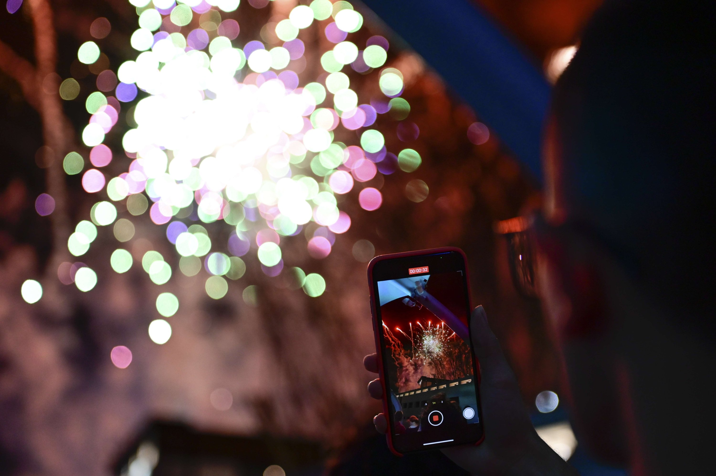 An onlooker takes a video from a cell phone during a fireworks display in preparation for Super Bowl LV, Tampa, Florida, Feb. 06, 2021. (AFP Photo)