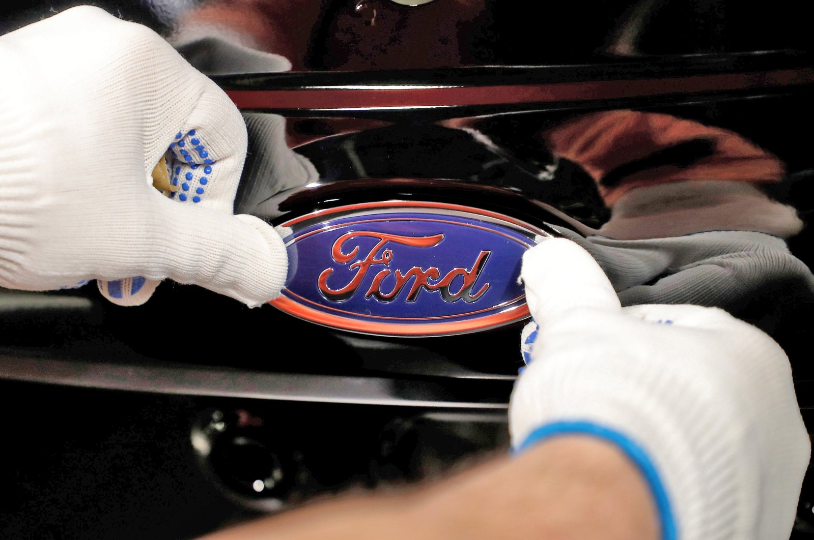 A worker attaches the Ford logo to a Fiesta car at the U.S. car manufacturer plant Ford in Cologne, Germany, Jan. 18, 2019. (EPA Photo)