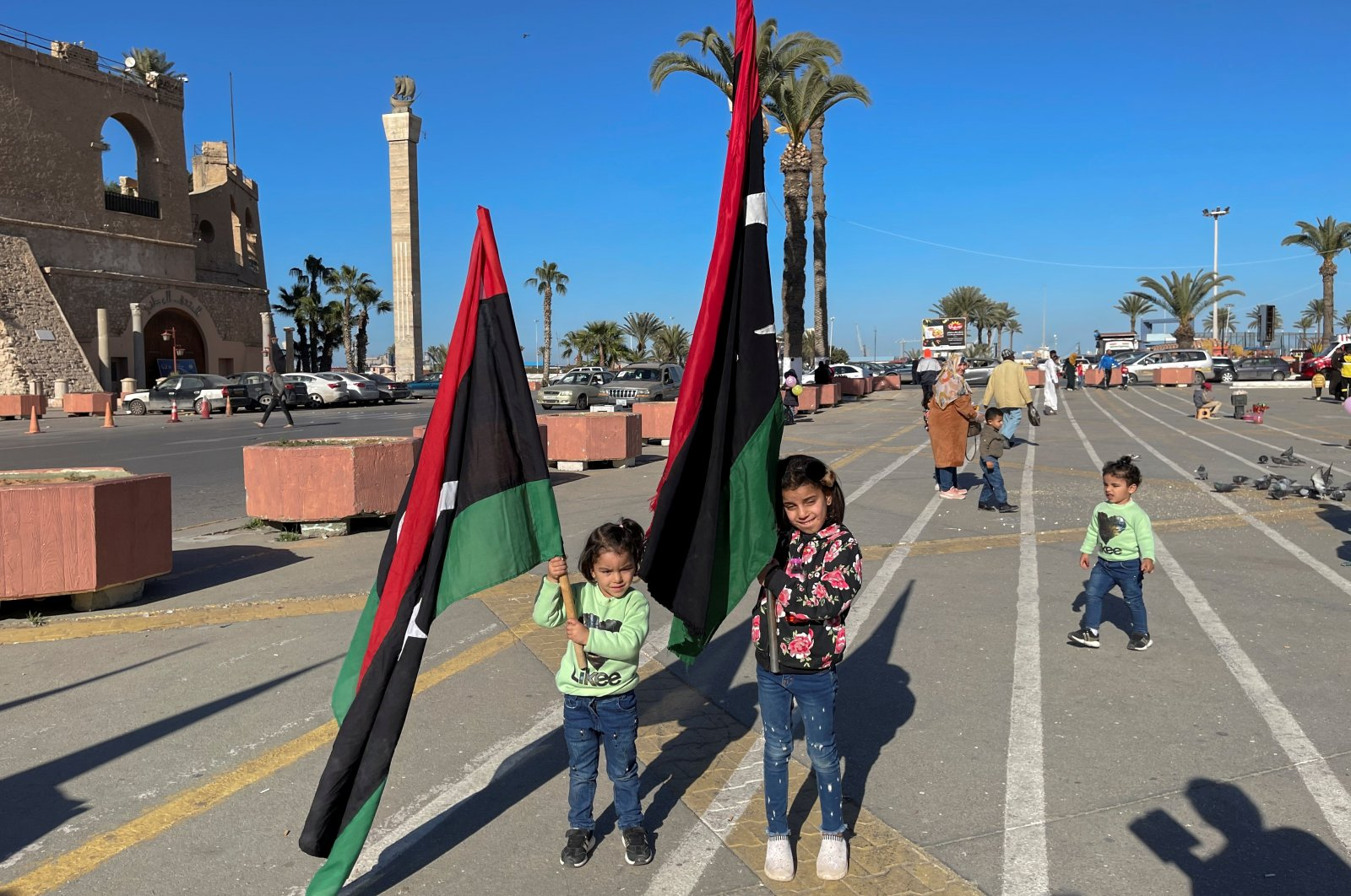 Children carrying Libyan flags pose for photos at Martyrs' Square in Tripoli, Libya, Feb. 5, 2021. (REUTERS)