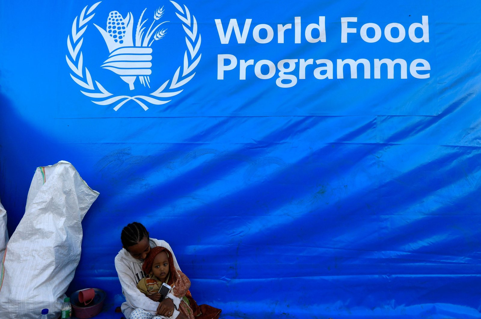 An Ethiopian woman, who fled the ongoing fighting in Tigray region, holds her child under a World Food Programme banner in Hamdayet village on the Sudan-Ethiopia border, in the eastern Kassala state, Sudan, Dec. 15, 2020. (Reuters Photo)