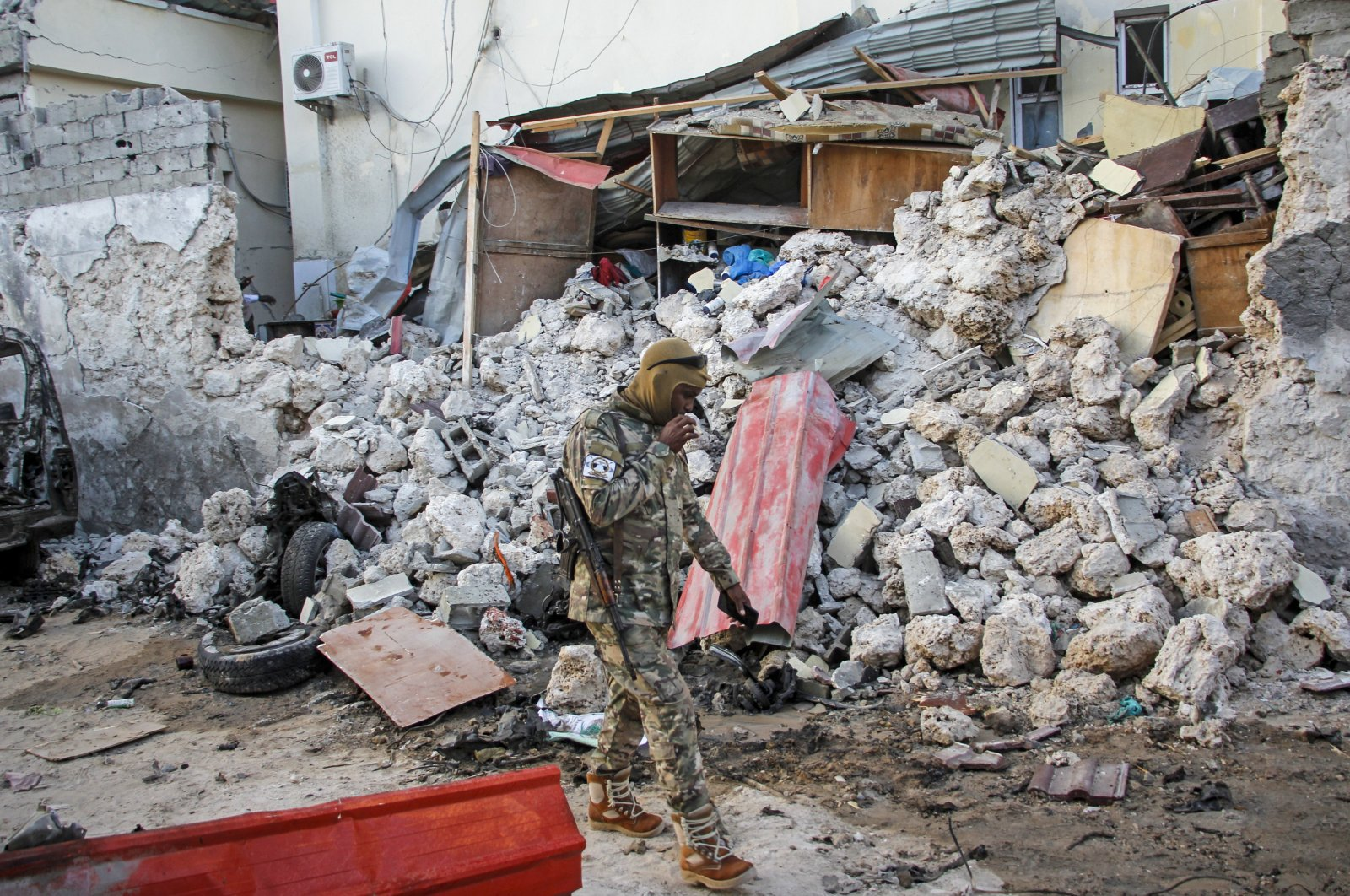 A soldier walks past wreckage in the aftermath of an attack on the Afrik hotel in Mogadishu, Somalia, Feb. 1, 2021. (AP Photo)