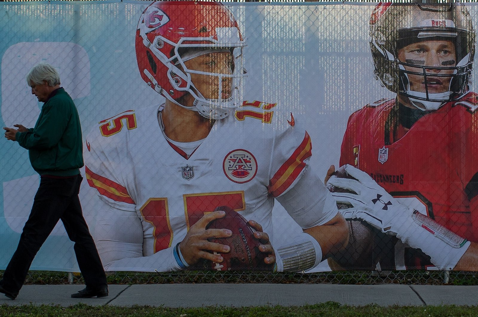 A pedestrian walks past a fence banner with the portraits of Super Bowl LV quarterback Patrick Mahomes (L) and Tom Brady, ahead of the NFL Super Bowl LV in Tampa, Florida, U.S., Feb. 4, 2021. (EPA Photo)