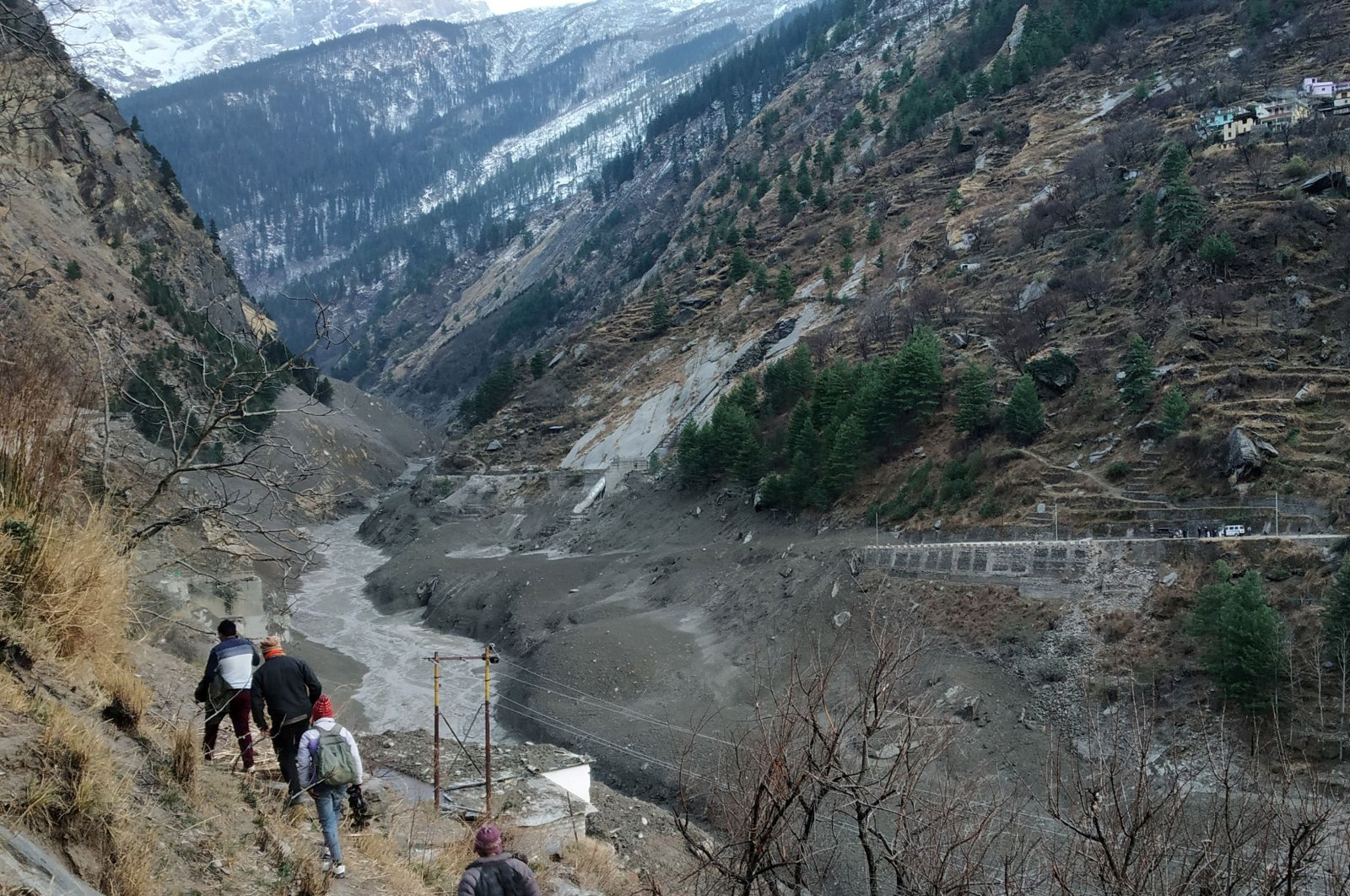 People walk past a destroyed dam after a Himalayan glacier broke and crashed at Raini Chak Lata village in the Chamoli district, in the northern state of Uttarakhand, India, Feb. 7, 2021. (Reuters Photo)