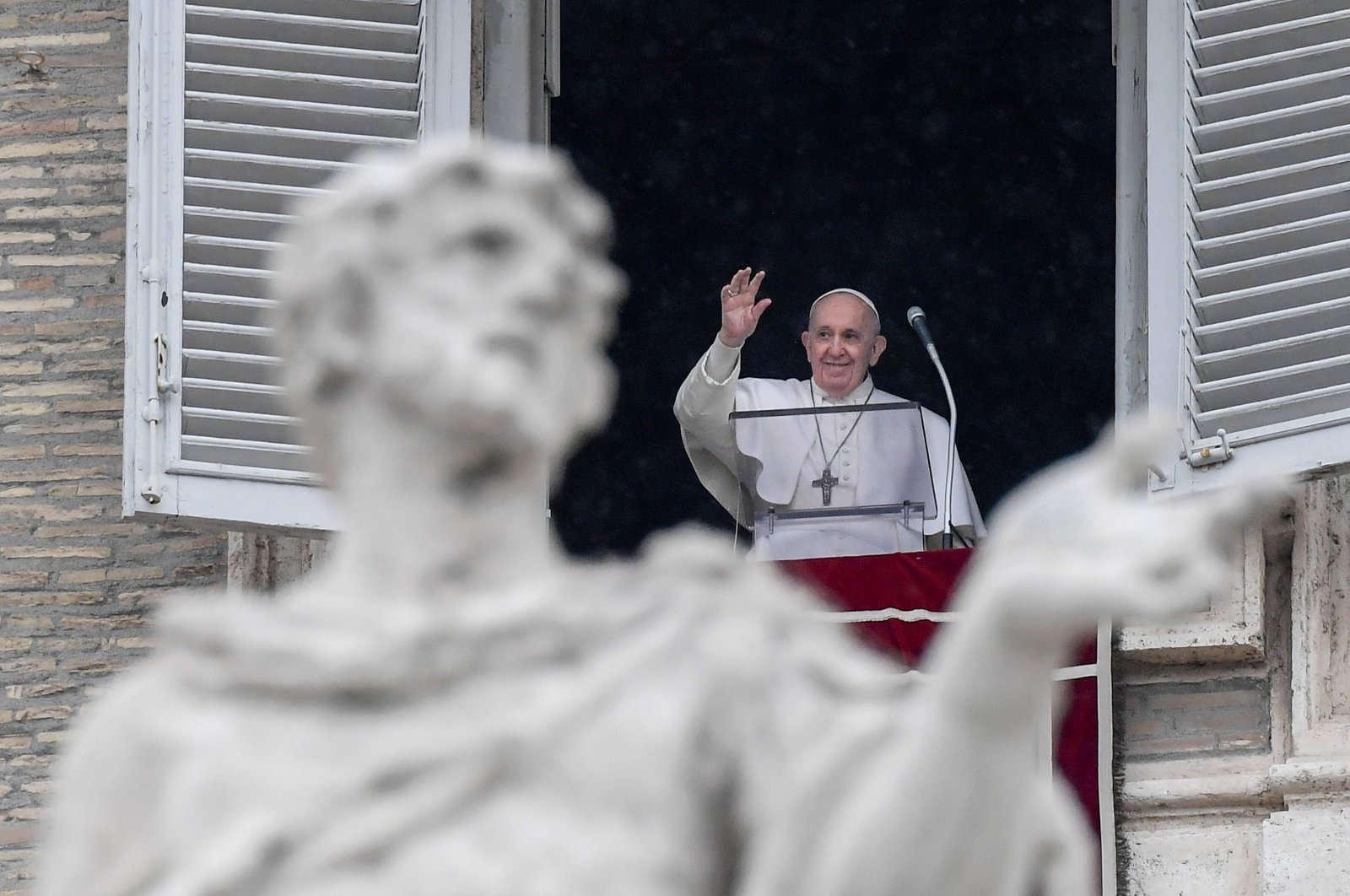 Pope Francis waves from the window of the Apostolic Palace overlooking St. Peter's Square during the weekly Angelus prayer on Feb. 7, 2021 in the Vatican (AFP)