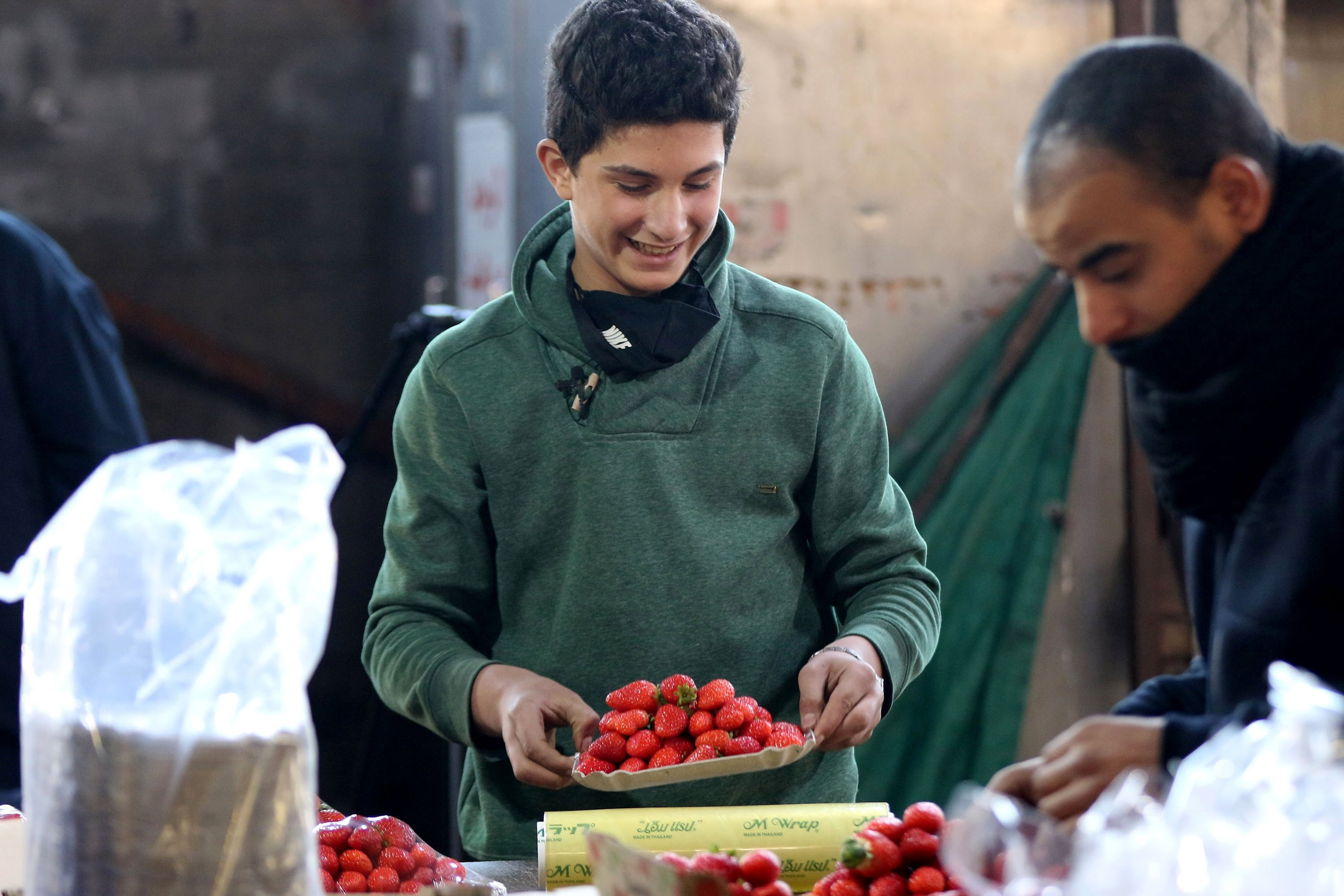 Mohammad, 14, arranges strawberry boxes in one of Amman's popular vegetable and fruit markets, Jordan, Jan. 10, 2021. (AFP Photo)