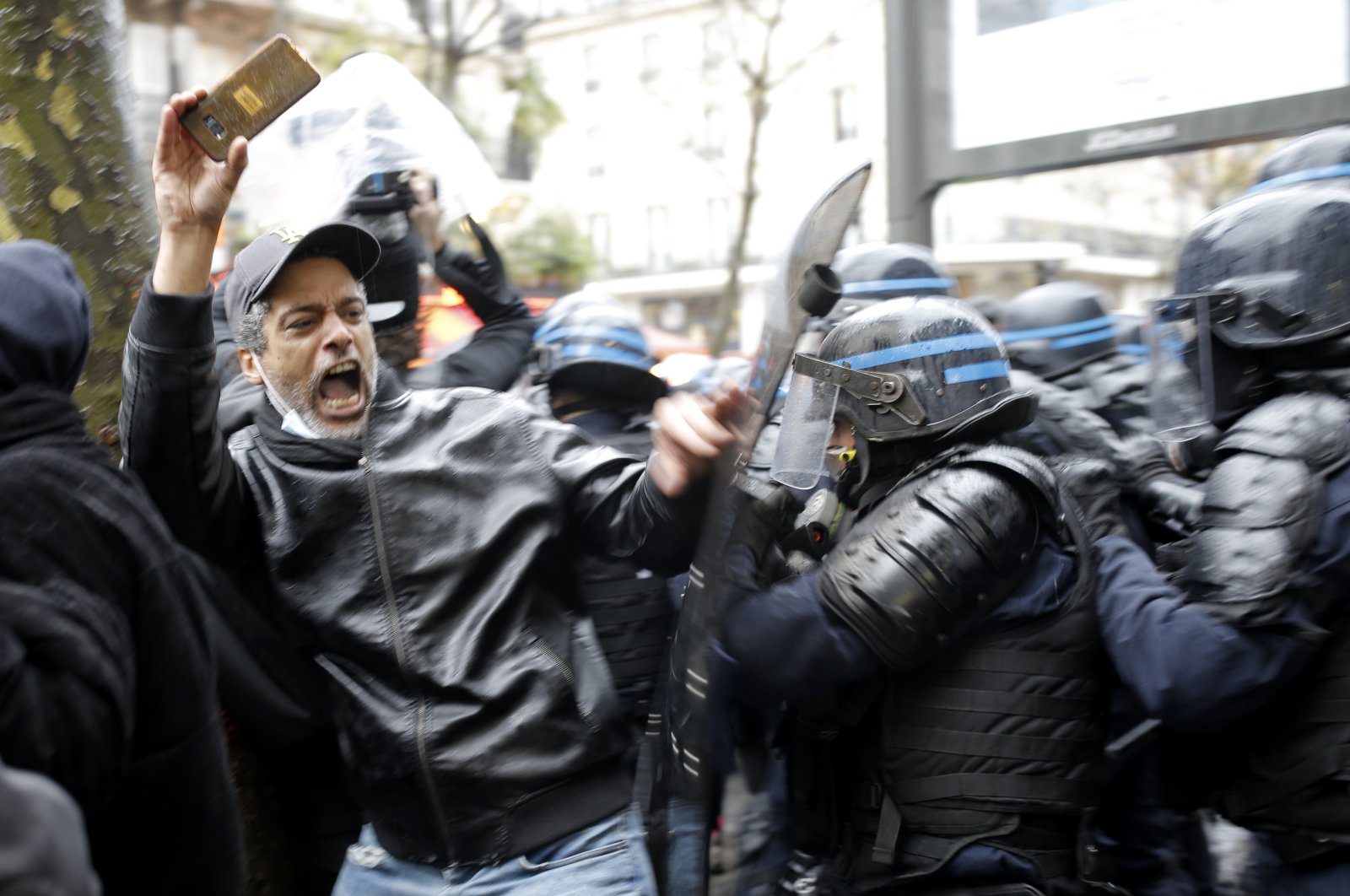 Riot police officers charge a man holding his phone during a protest in Paris, France, Dec. 12, 2020. (AP Photo)