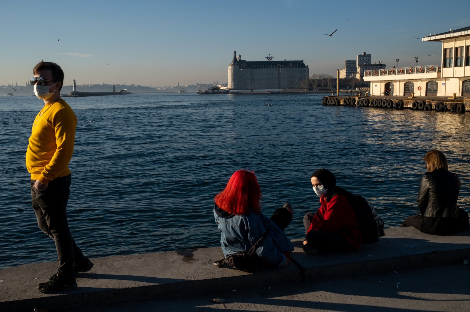 People spend time at a seaside amid the COVID-19 pandemic, Kadıköy district, Istanbul, Turkey, Feb. 5, 2021. (Photo by Getty Images)