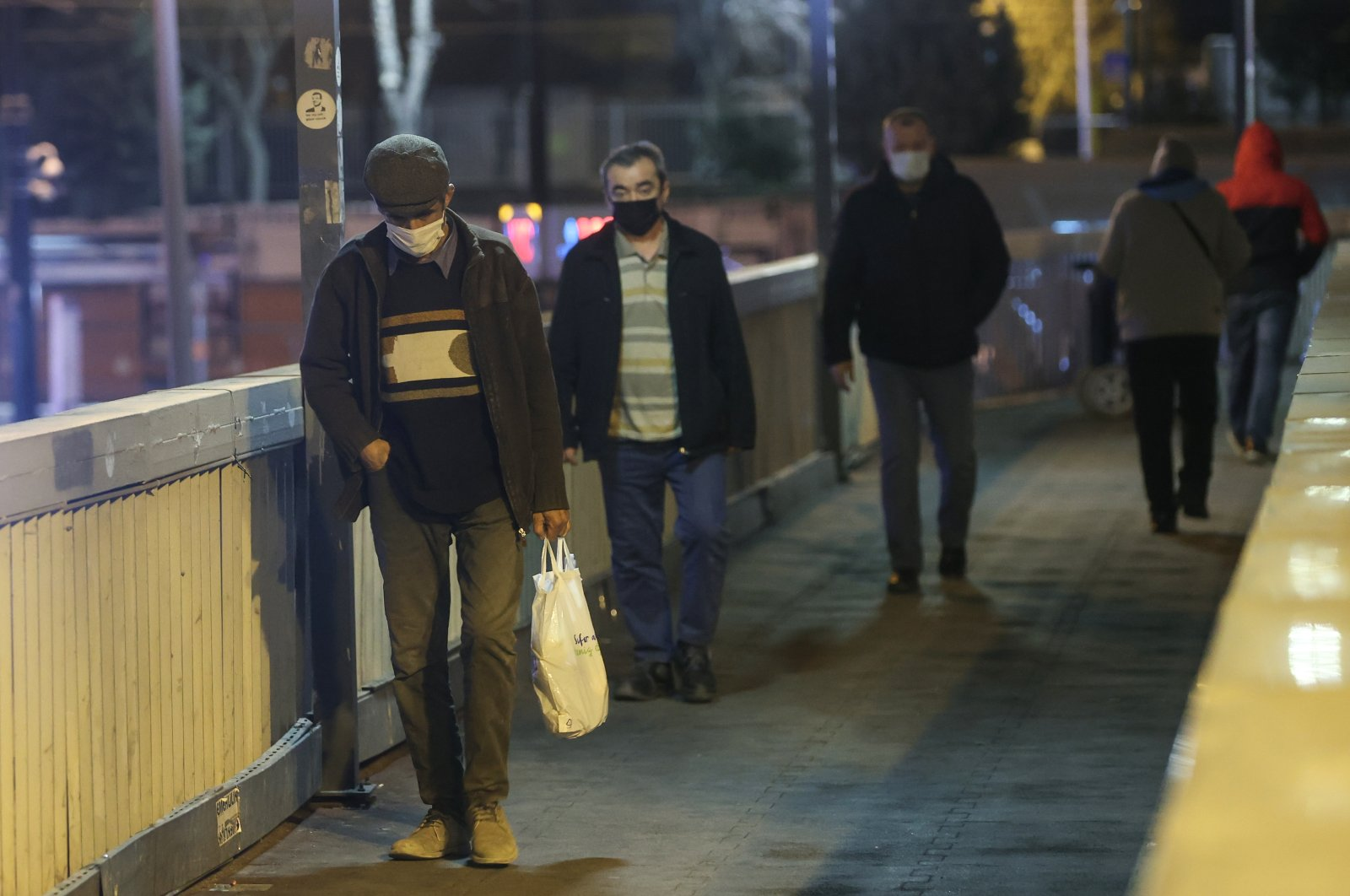 People wearing protective masks walk on an overpass, in Istanbul, Turkey, Feb. 8, 2021. (AA Photo)