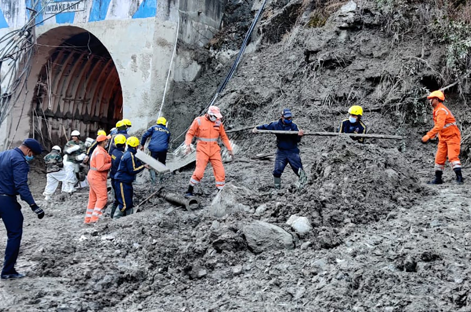 This photograph provided by National Disaster Response Force shows personnel preparing to rescue workers at one of the hydropower projects at Reni village in Chamoli district of the Indian state of Uttarakhand, Monday, Feb. 8, 2021.(National Disaster Response Force via AP)