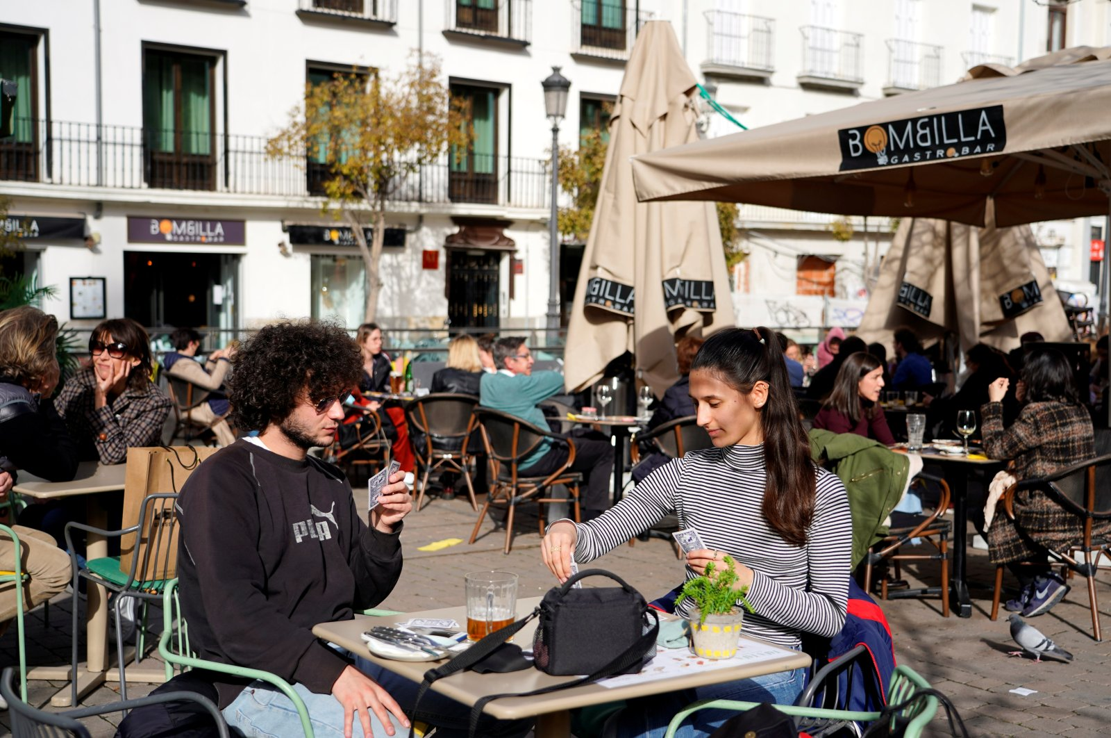 French visitors Theo Perucci and his sister Luna play cards while enjoying a meal on a terrace during their week on holiday as the coronavirus pandemic continues in Madrid, Spain, Feb. 5, 2021. (Reuters Photo)