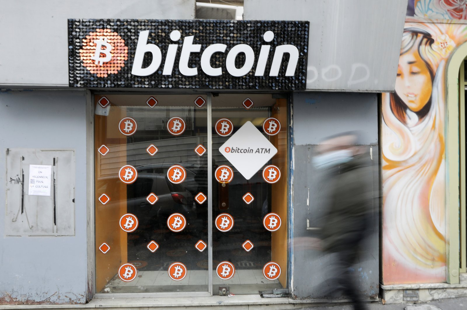A man wearing a protective mask walks past a Bitcoin digital currency ATM shop in Marseille, France, Feb. 7, 2021. (Reuters Photo)