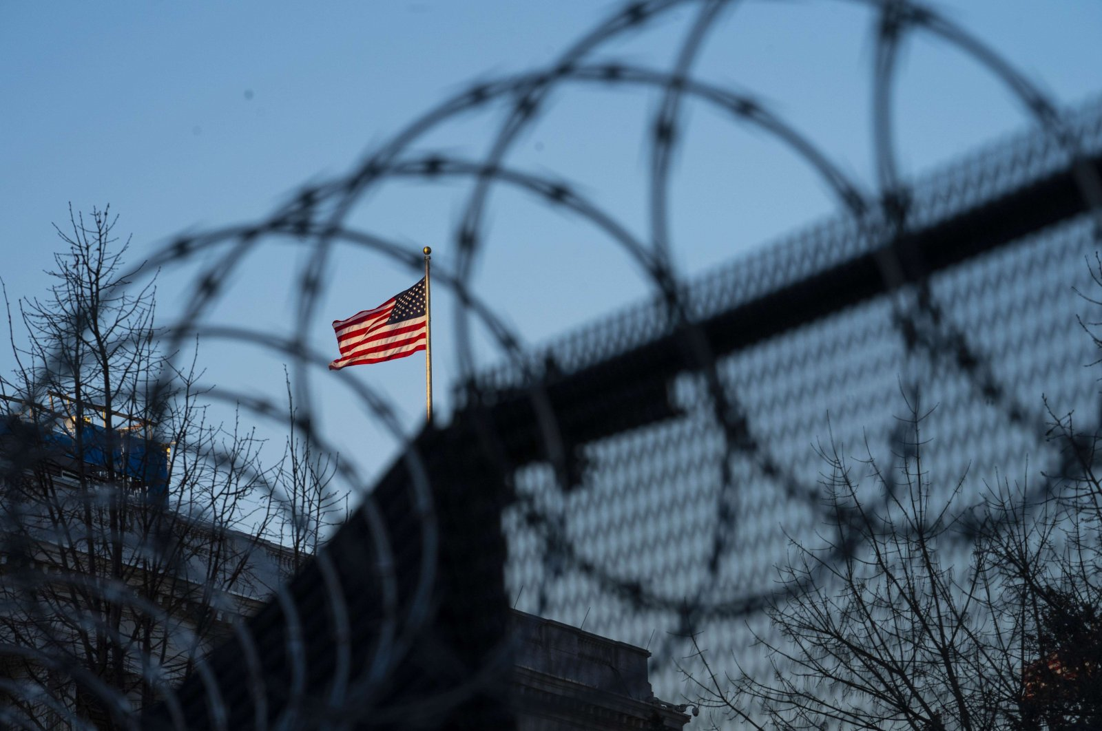 An American flag is seen through barbed wire fencing at sunrise on Capitol Hill in Washington, D.C., on Feb. 8, 2021. (AFP Photo)