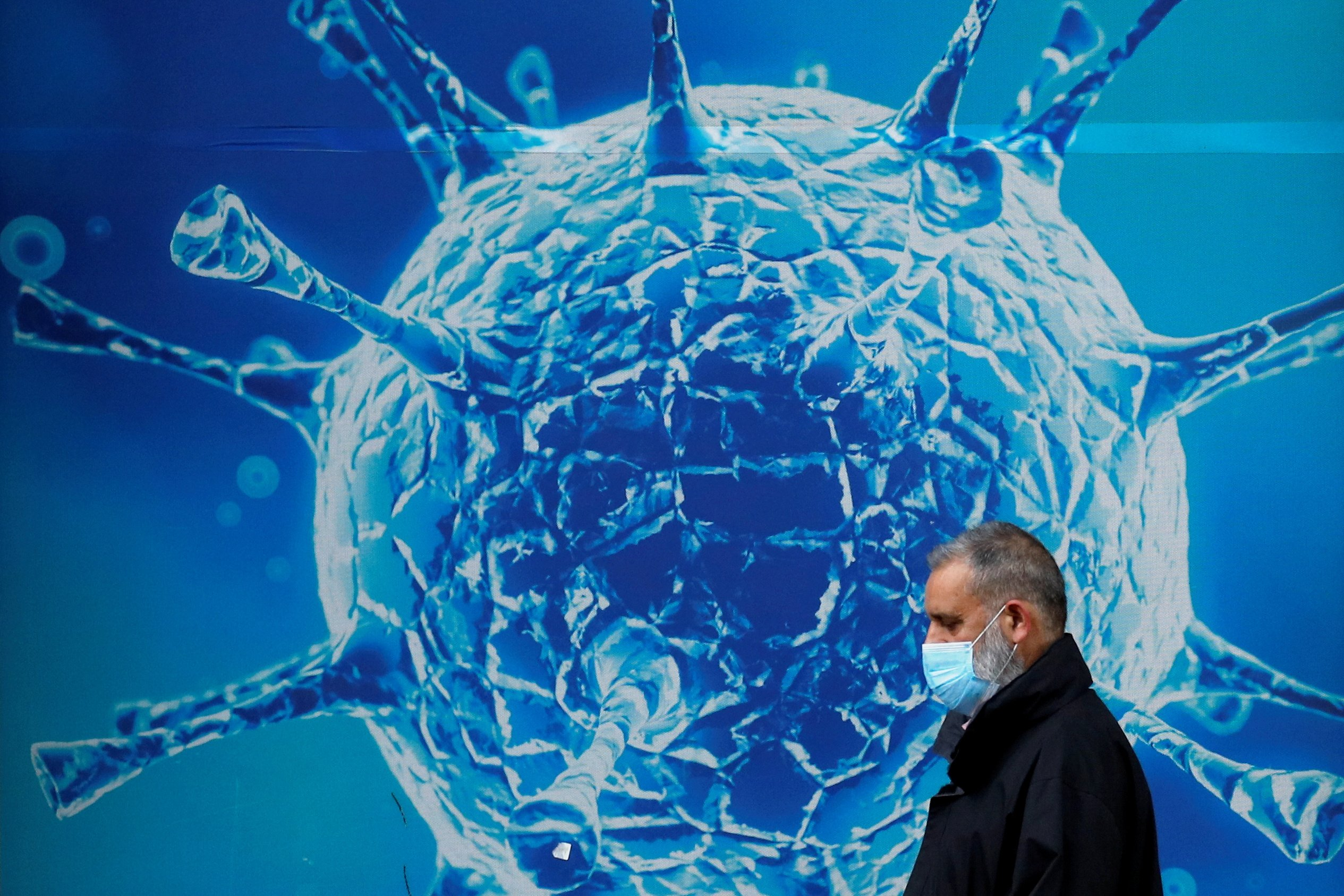 A man wearing a protective face mask walks past an illustration of a virus outside a regional science center amid the coronavirus disease (COVID-19) outbreak, in Oldham, Britain, August 3, 2020. (REUTERS Photo=