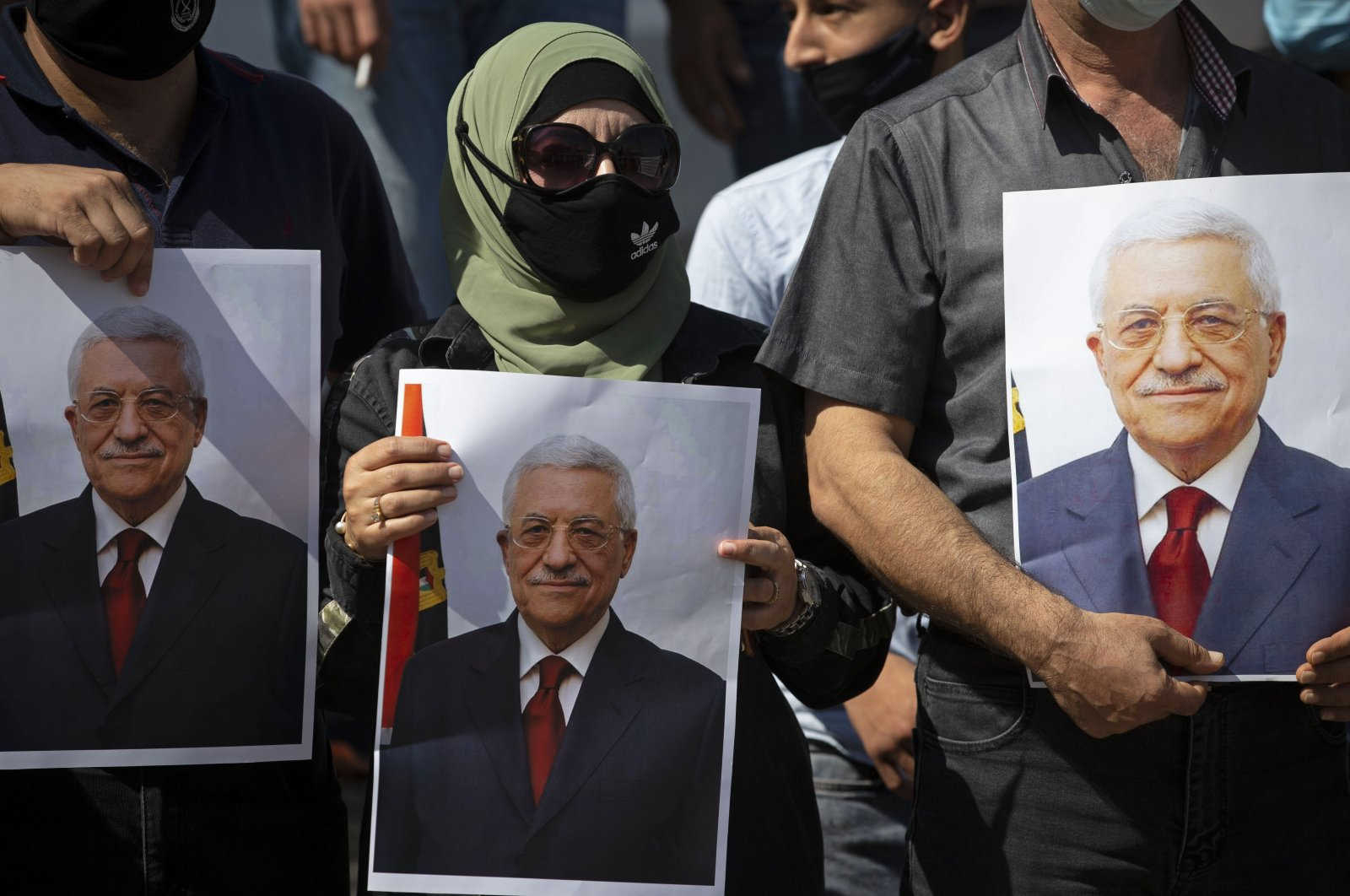 Palestinians hold pictures of Palestinian President Mahmoud Abbas during a rally to support Abbas, in the West Bank town of Tubas, Palestine, Sept. 27, 2020. (AP Photo)