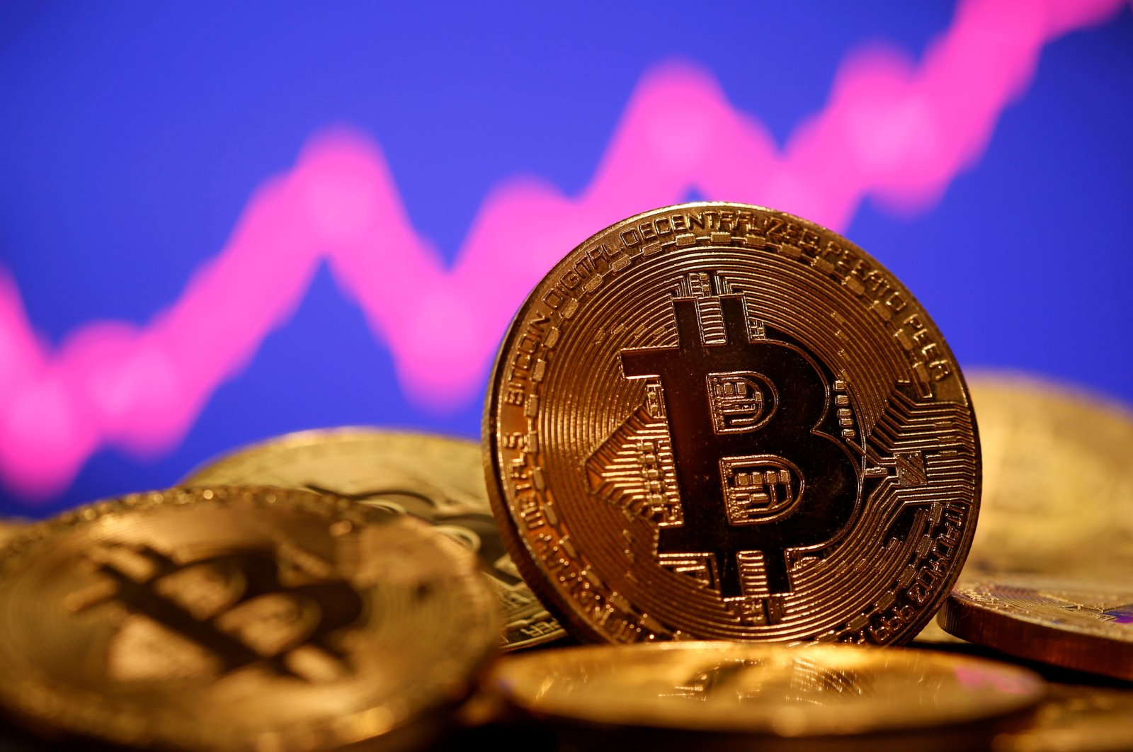A representation of virtual currency Bitcoin is seen in front of a stock graph in this illustration, Jan. 8, 2021. (Reuters Photo)