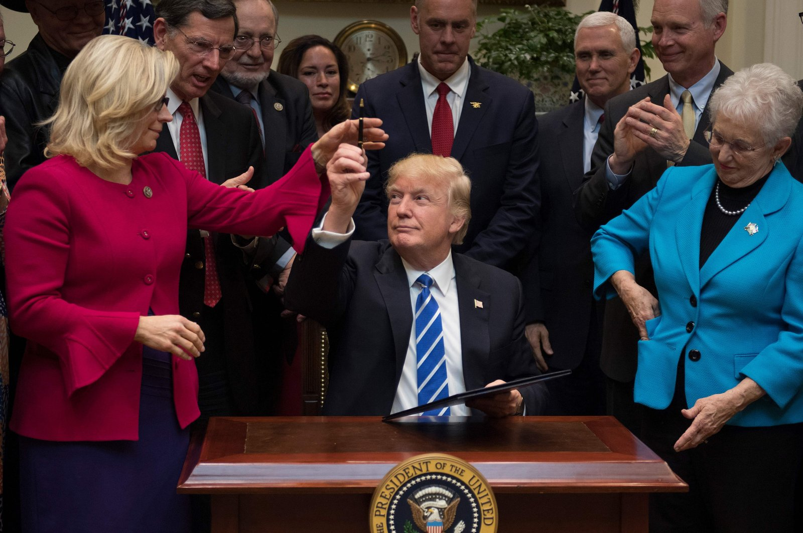 U.S. President Donald Trump gives a pen to U.S. Congressperson Liz Cheney (L), R-Wyoming, after signing H.J. Resolution 37, 44, 57 and 58 at the White House in Washington, DC., U.S. March 27, 2017. (AFP Photo)