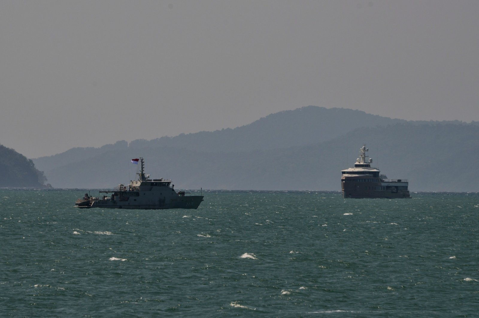 """An Indonesian naval ship (L) escorts the Russian superyacht """"La Datcha George Town"""" near the coast of Aceh province, in Banda Aceh, Indonesia, Feb. 8, 2021. ( AFP Photo)"""