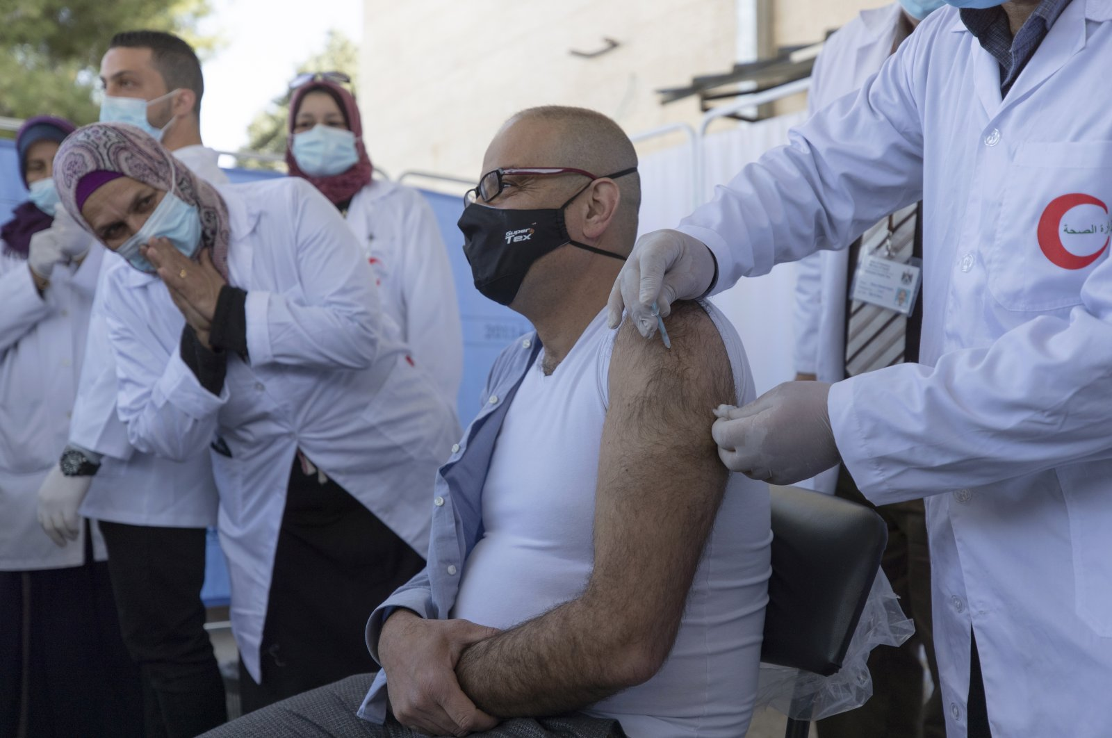 A medic administers a Moderna COVID-19 vaccine to a fellow medic during a campaign to vaccinate front-line medical workers, at the health ministry, in Bethlehem, the West Bank, Palestine, Feb. 3, 2021. (AP Photo)