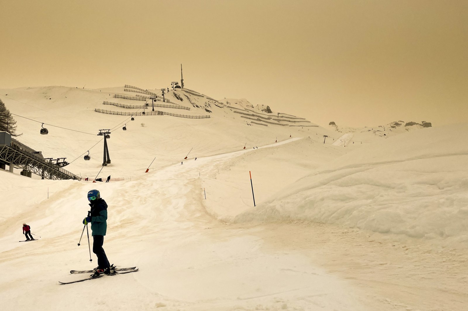 A skier wearing a protective face mask skis as Sahara sand colors the snow and sky in orange creating a special light atmosphere, during the coronavirus outbreak, in the Alpine resort of Anzere, Switzerland, Feb. 6, 2021. (AP Photo)