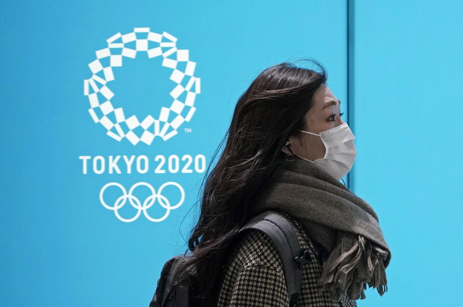 A woman walks past a postponed Tokyo Olympic Games advertising board in Tokyo, Japan, Jan. 27, 2021. (EPA Photo)