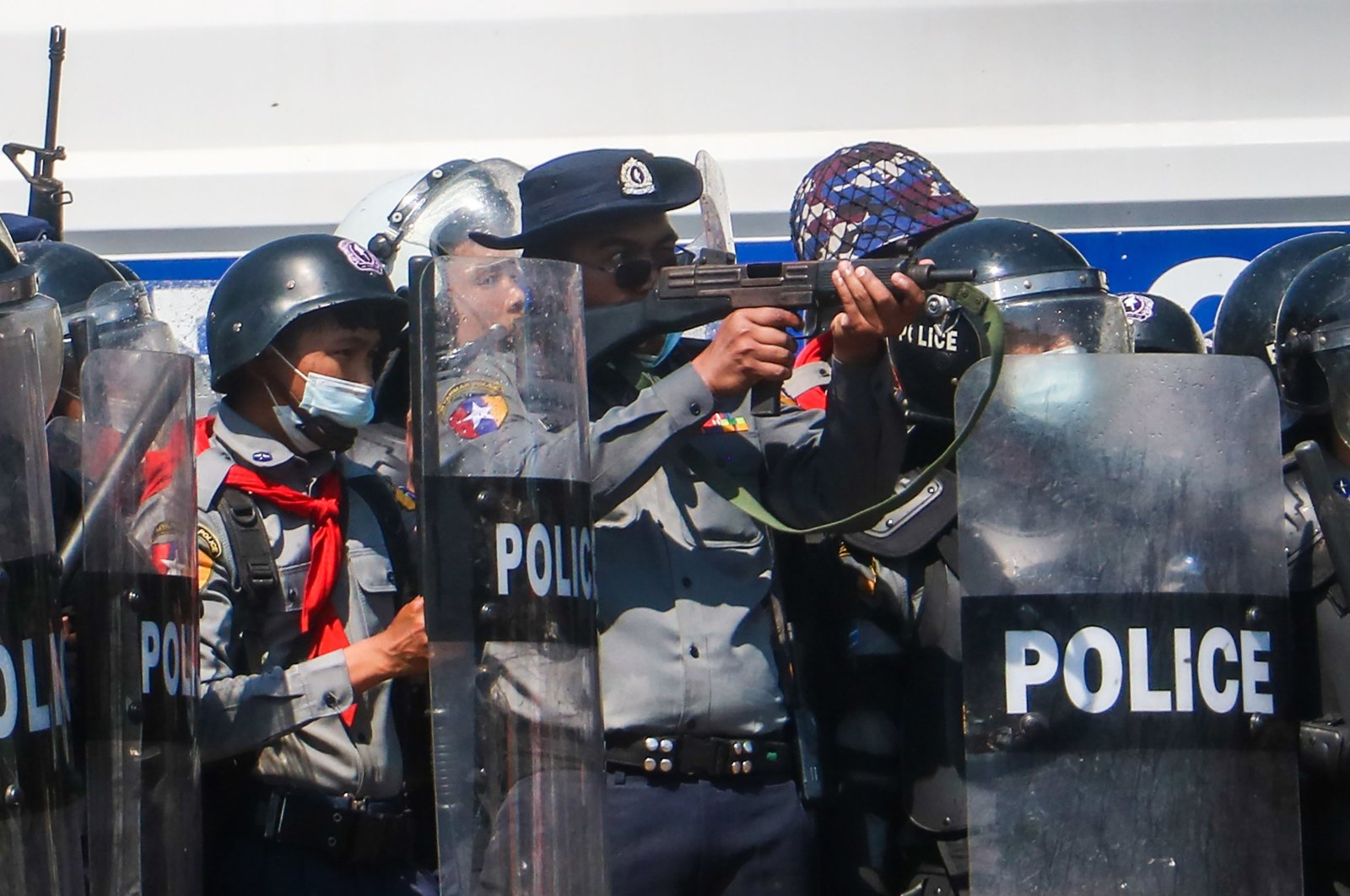 A police officer (C) aims a gun during clashes with protesters taking part in a demonstration against the military coup in Naypyitaw, Myanmar, Feb. 9, 2021. (AFP Photo)