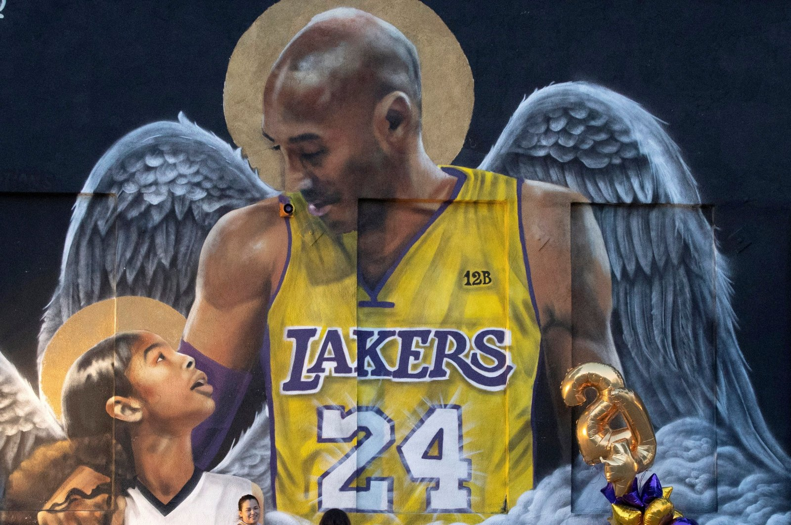 A fan poses by a mural of late Kobe Bryant, who perished one year ago alongside his daughter and seven others when their helicopter crashed into a hillside, in Los Angeles, California, U.S., Jan. 26, 2021. (Reuters)