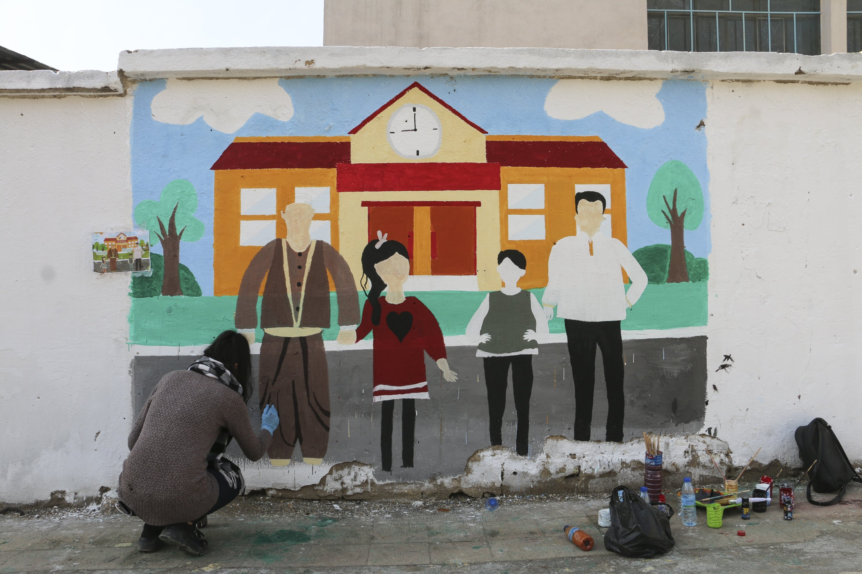A group of young people decorates the walls of northern Syria's Afrin town with drawings, Feb. 10, 2021. (AA Photo)