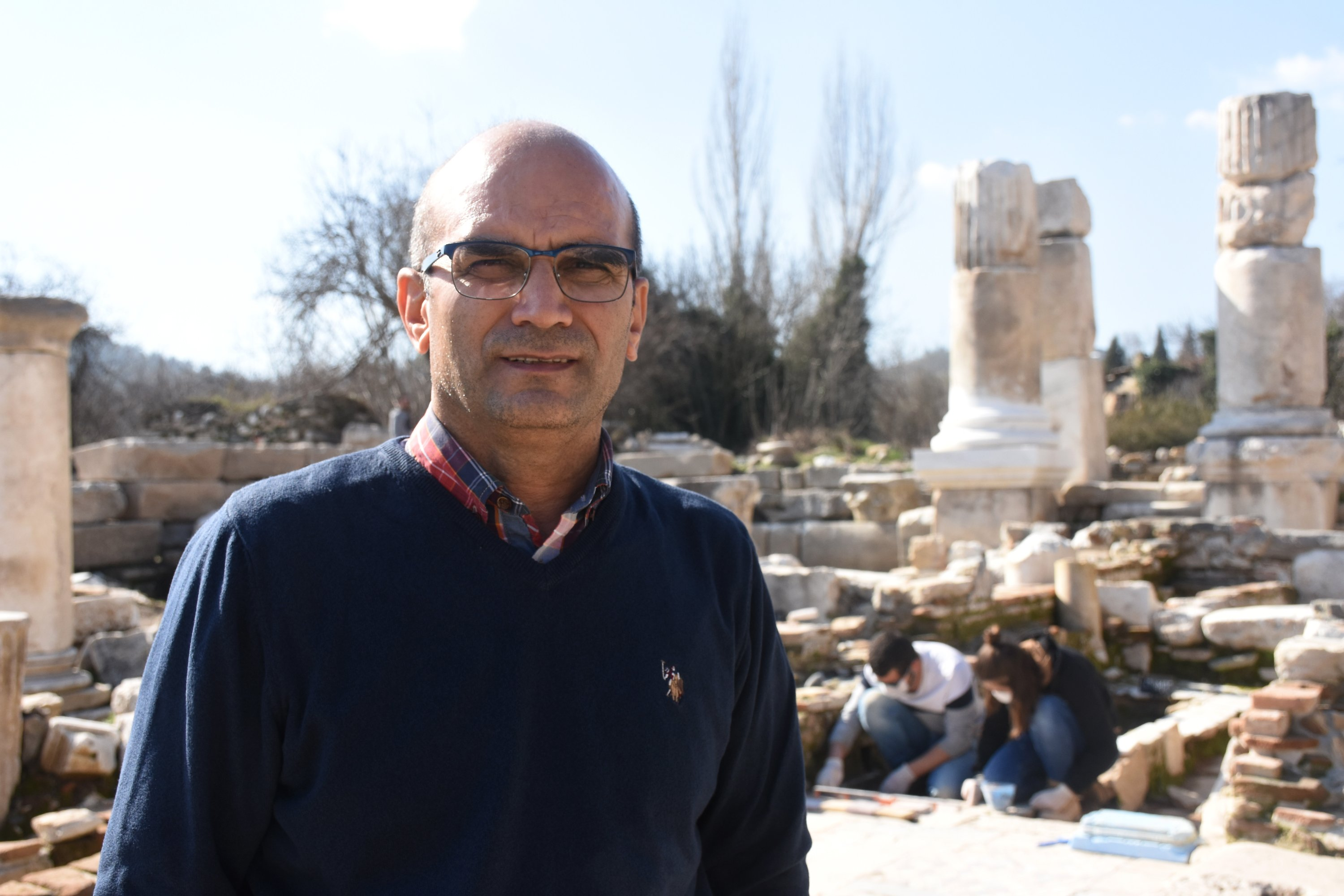 Professor Bilal Söğüt of Pamukkale University, head of excavations in Stratonikeia, stands at the ancient site while restorative work continues, Muğla, southwestern Turkey, Feb. 9, 2021. (AA Photo)
