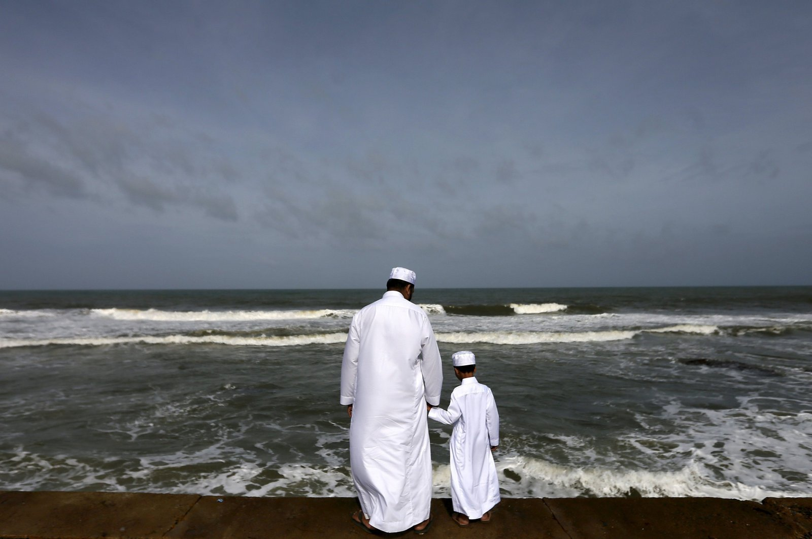 A Sri Lankan Muslim father and son stand in front of the sea during morning prayers of Eid al-Fitr celebrations marking the end of Ramadan, in Colombo, July 18, 2015. (Reuters Photo)