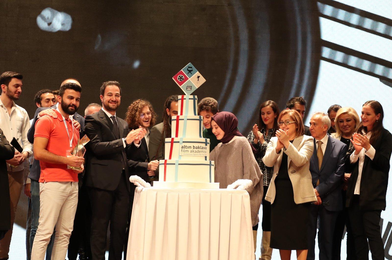 Winners of the Golden Baklava Film Academy Fifth International Student Film Festival cut a cake at the celebration in Gaziantep, southeastern Turkey, 2019.
