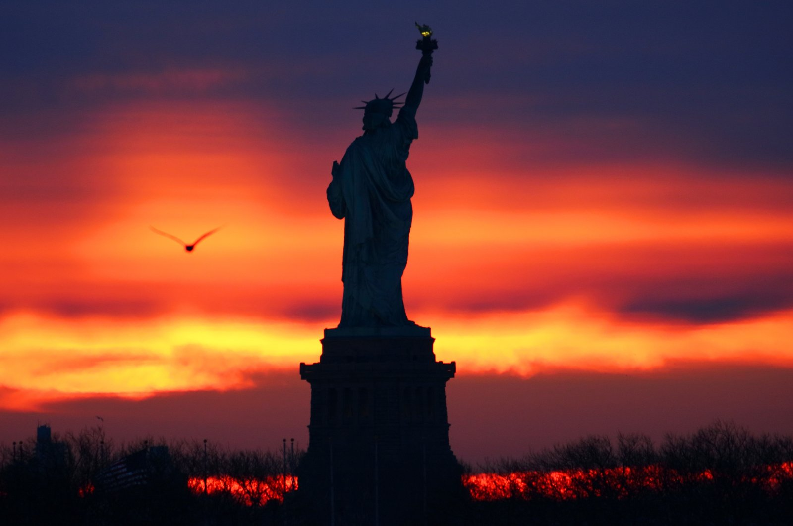 The sun rises behind the Statue of Liberty in New York City as seen from Jersey City, New Jersey, the U.S., Feb. 6, 2021. (Photo by Getty Images)