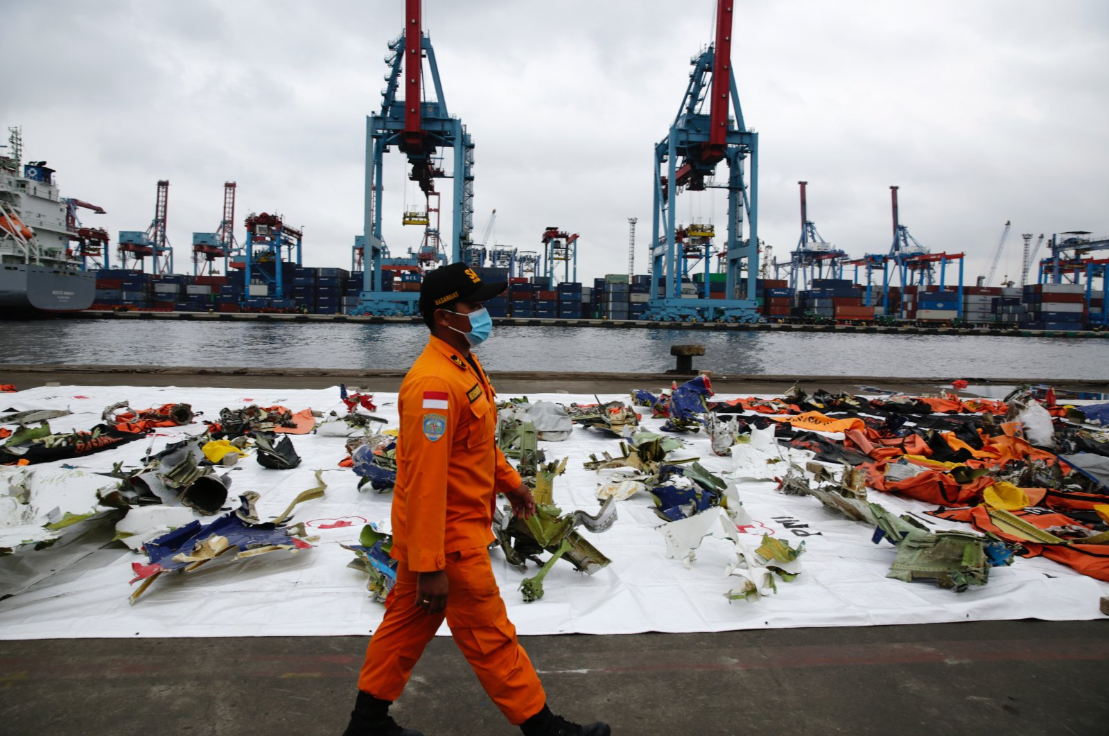 A member of Indonesia's National Search and Rescue Agency (BASARNAS) walks past the debris of Sriwijaya Air flight SJ 182 plane recovered from the crash site in the waters off Jakarta at Tanjung Priok port in Jakarta, Indonesia, Jan. 17, 2021. (EPA Photo)