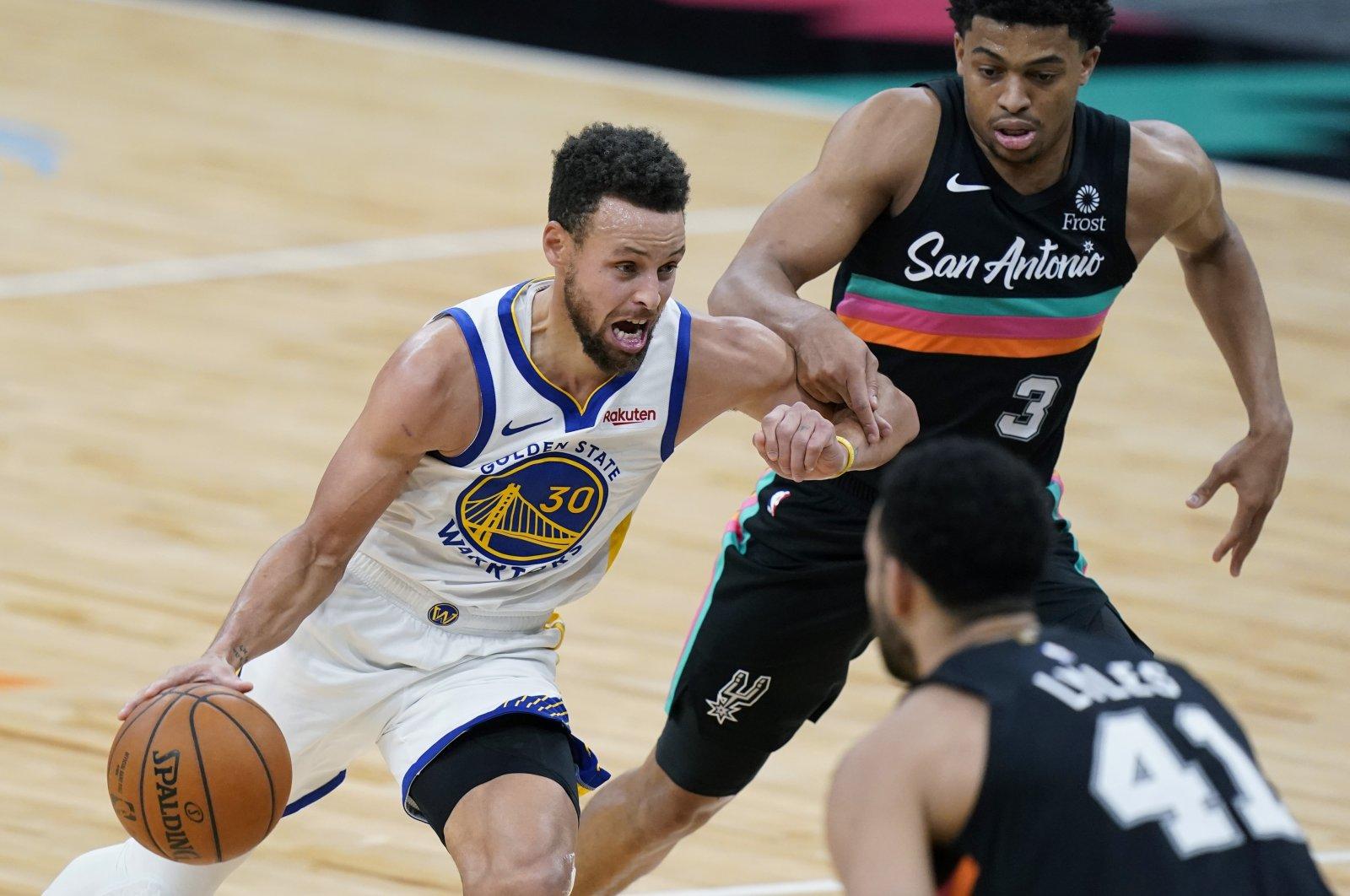 Golden State Warriors guard Stephen Curry (L) drives past San Antonio Spurs forward Keldon Johnson (R) during an NBA game in San Antonio, Tuesday, Feb. 9, 2021. (AP Photo)