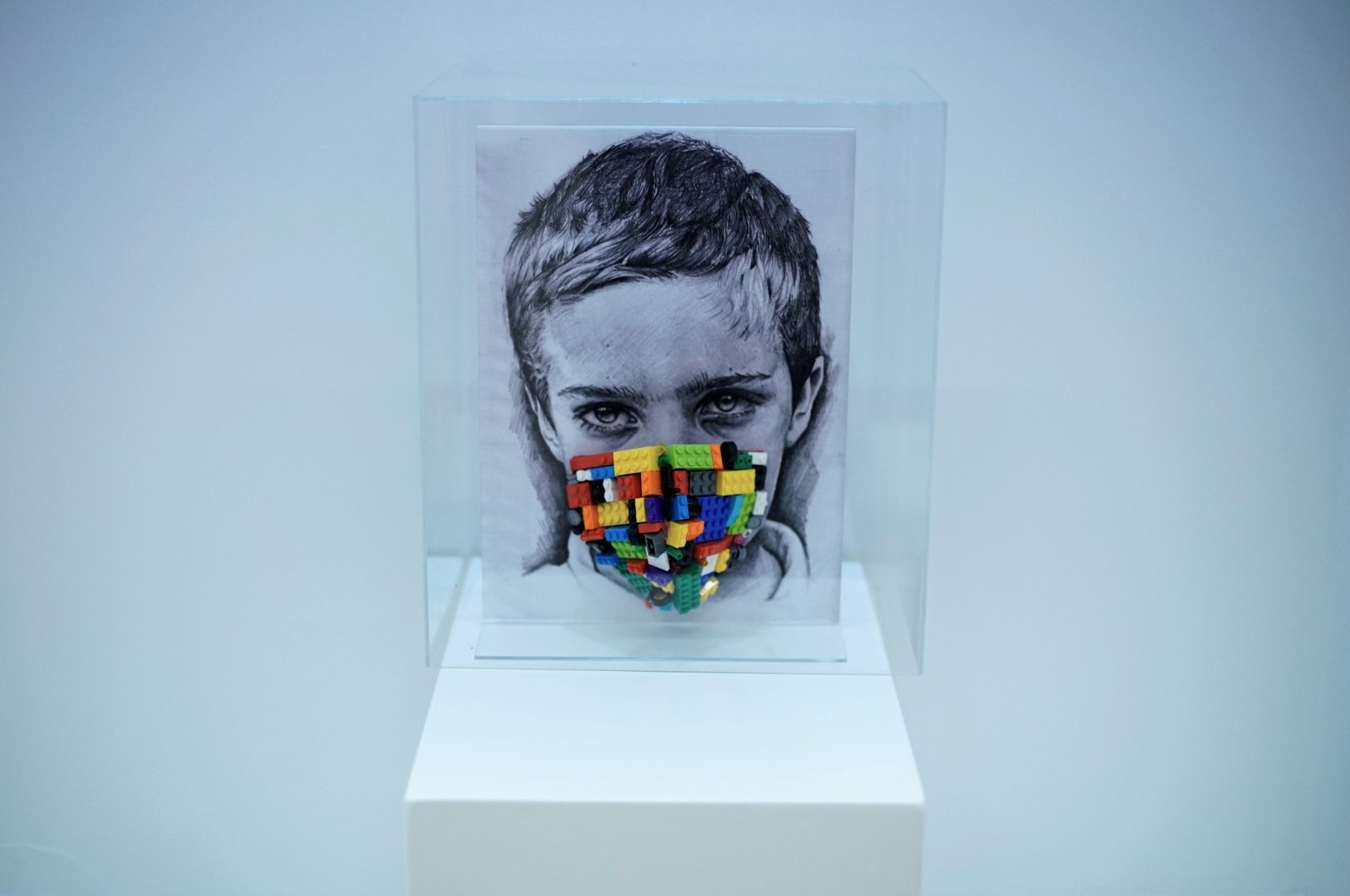"""Simay Bülbül, """"Childhood in the Glass Lantern,"""" installation of Lego pieces, plexi, textile, 33 by 24 centimeters."""